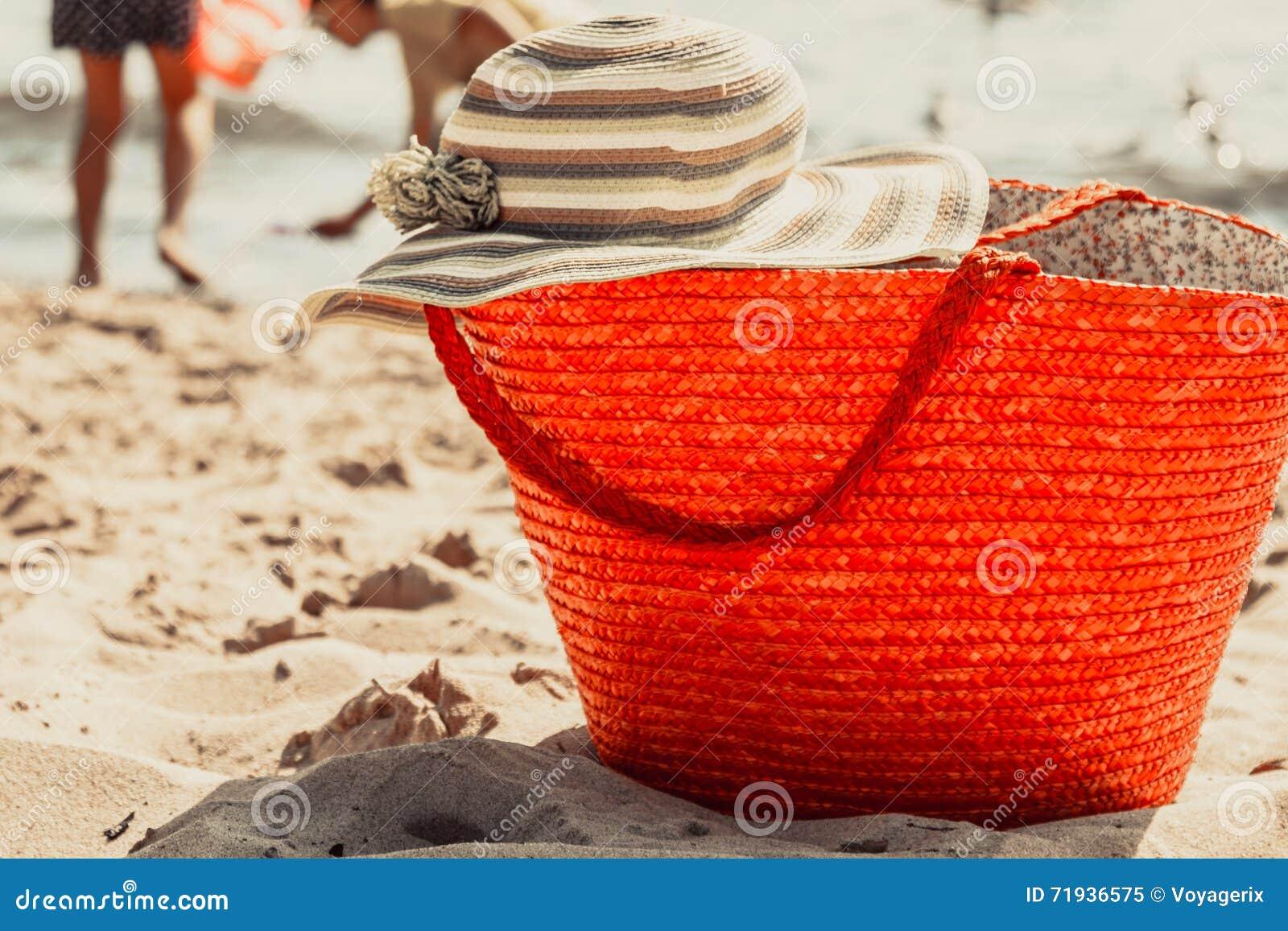 Сумка и шляпа сумки плетеной корзины на лете приставают к берегу