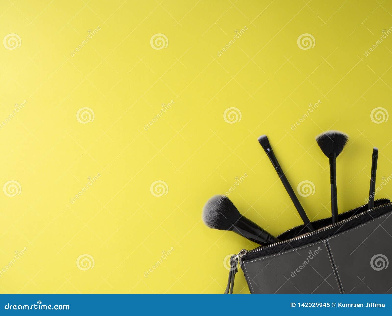 Сумка с щетками макияжа, косметиками, желтой предпосылкой