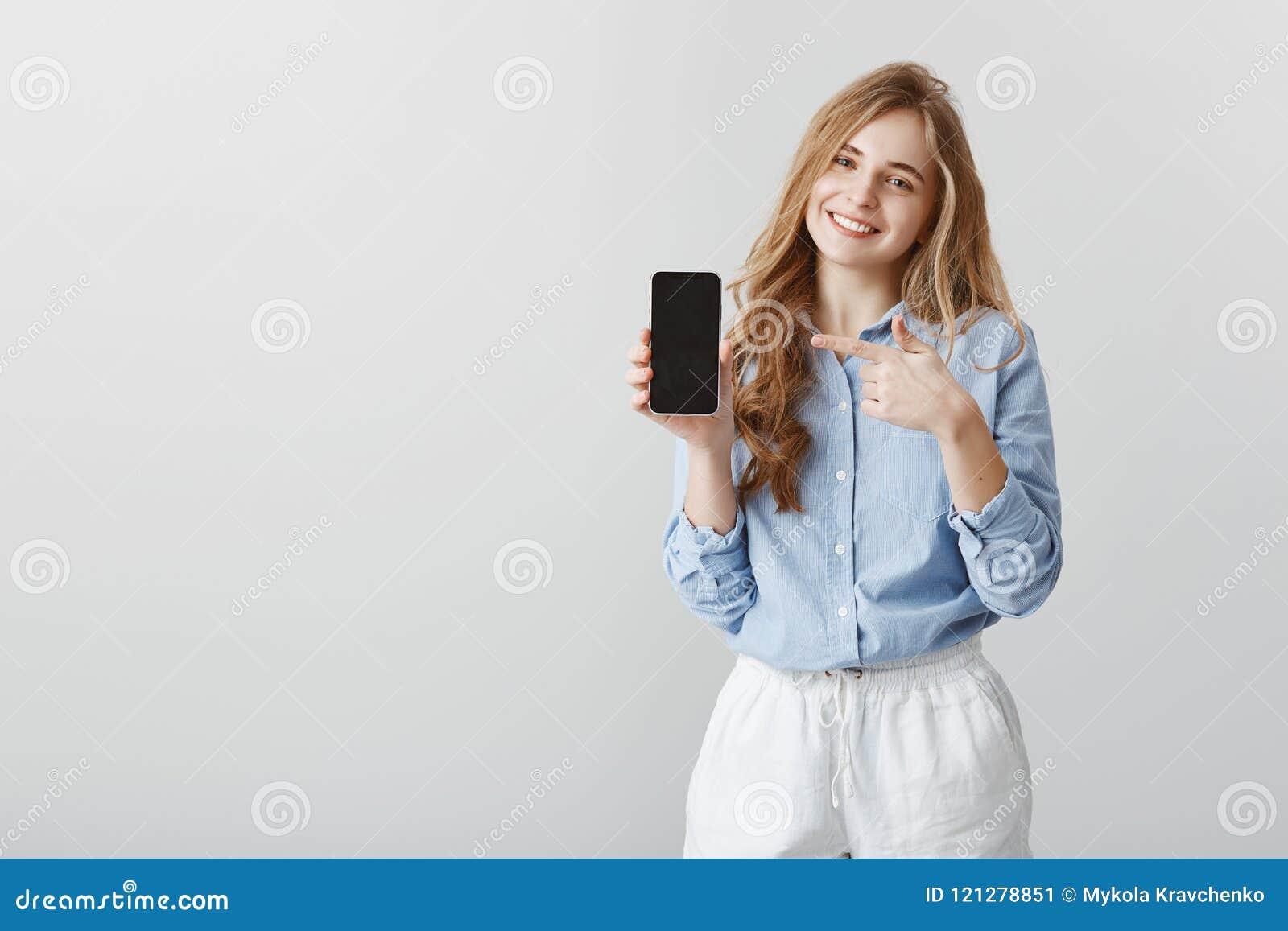 Супер полезный прибор Студия сняла довольной симпатичной студентки с светлыми волосами в рабочей рубашке, показывающ