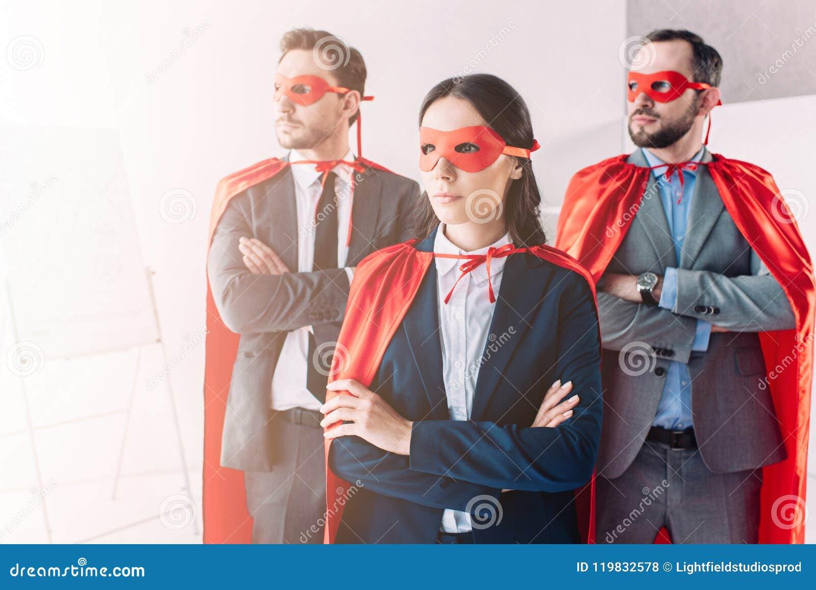 супер предприниматели в масках и накидки смотря прочь с пересеченными оружиями