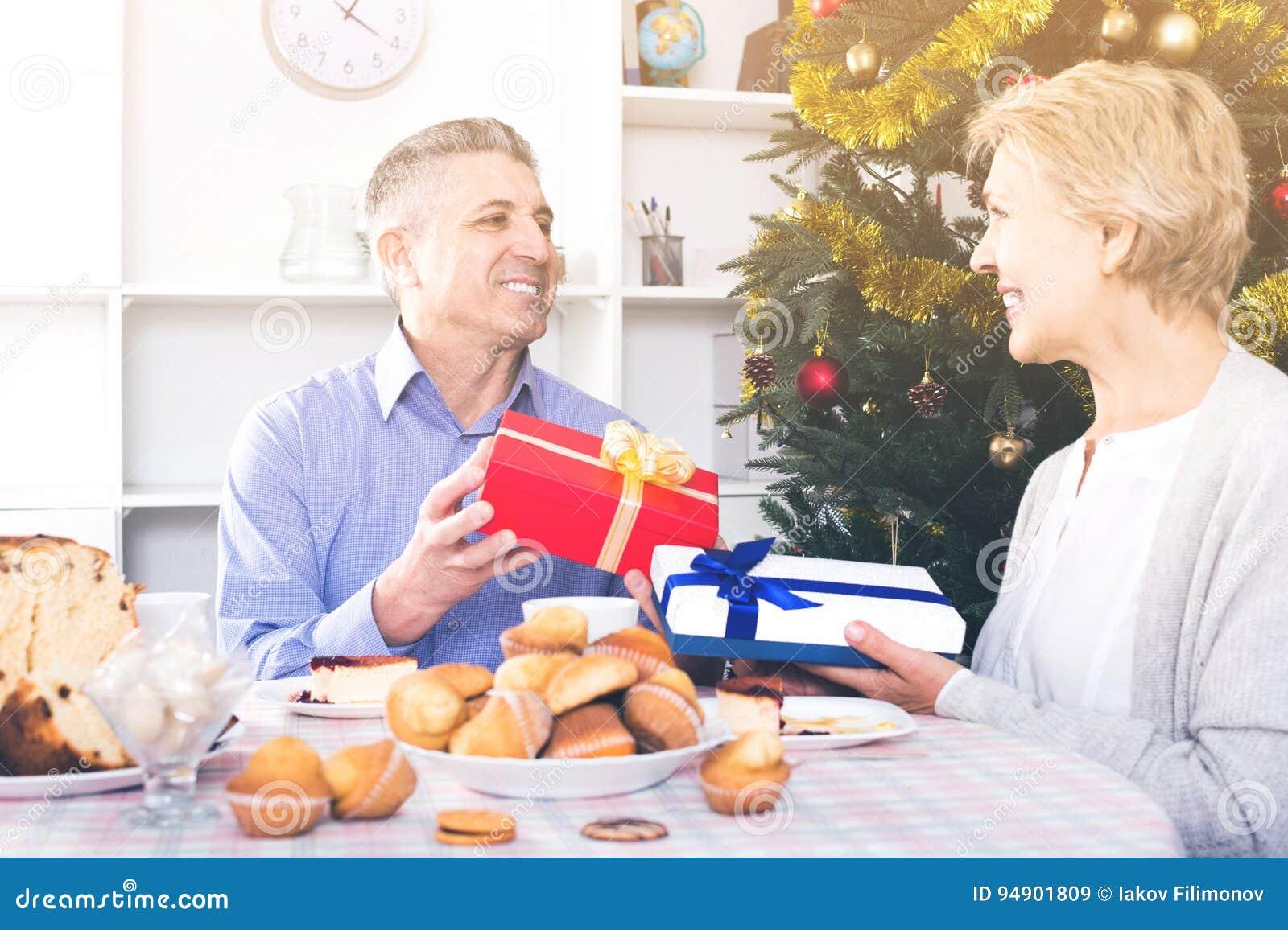 Супруг и жена обменивают праздничные подарки для рождества и нового Ye