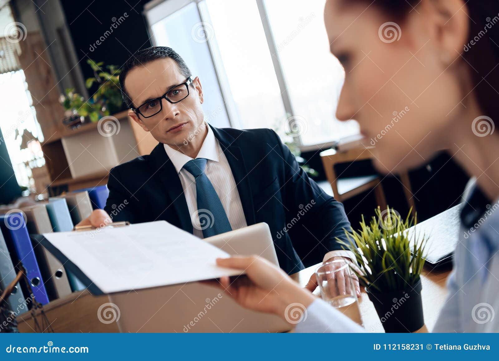 Супруг и жена подписывают поселение развода Пары идя через бумаги подписания развода