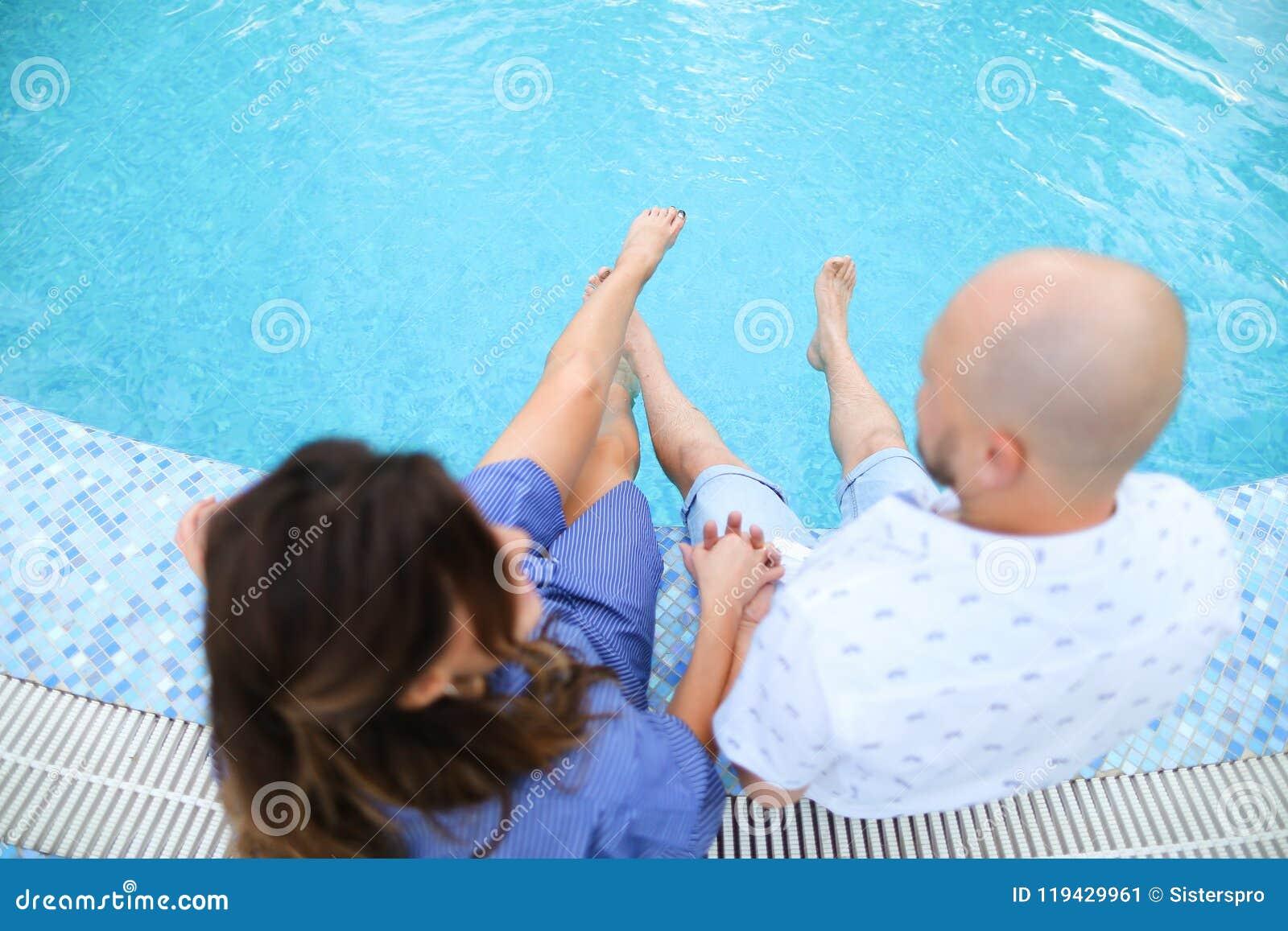 Супруг и жена сидя босоногий близко бассейн
