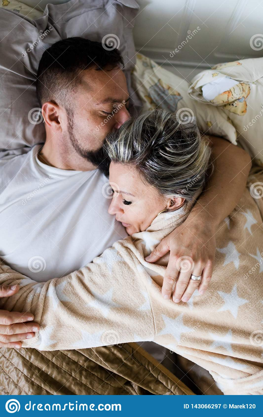 Супруг и жена спать совместно в одной кровати - в объятии