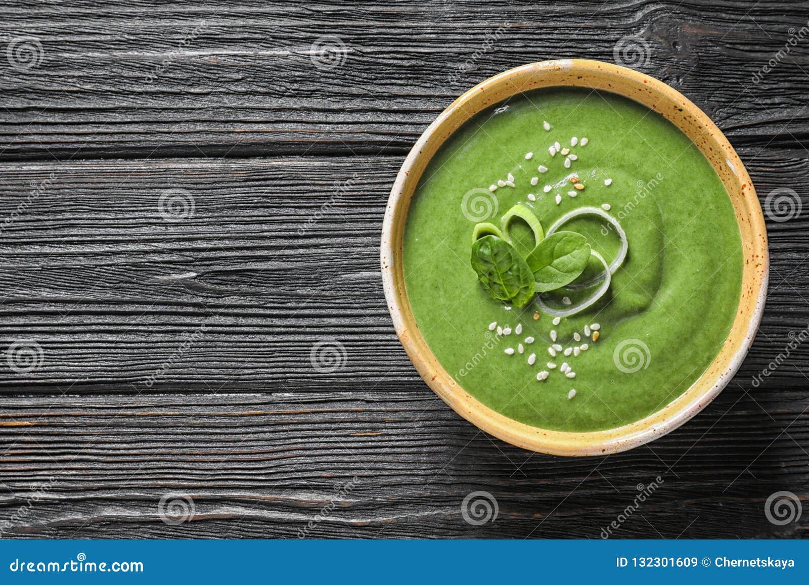 Суп вытрезвителя свежего овоща сделанный шпината в блюде на деревянной предпосылке, взгляде сверху