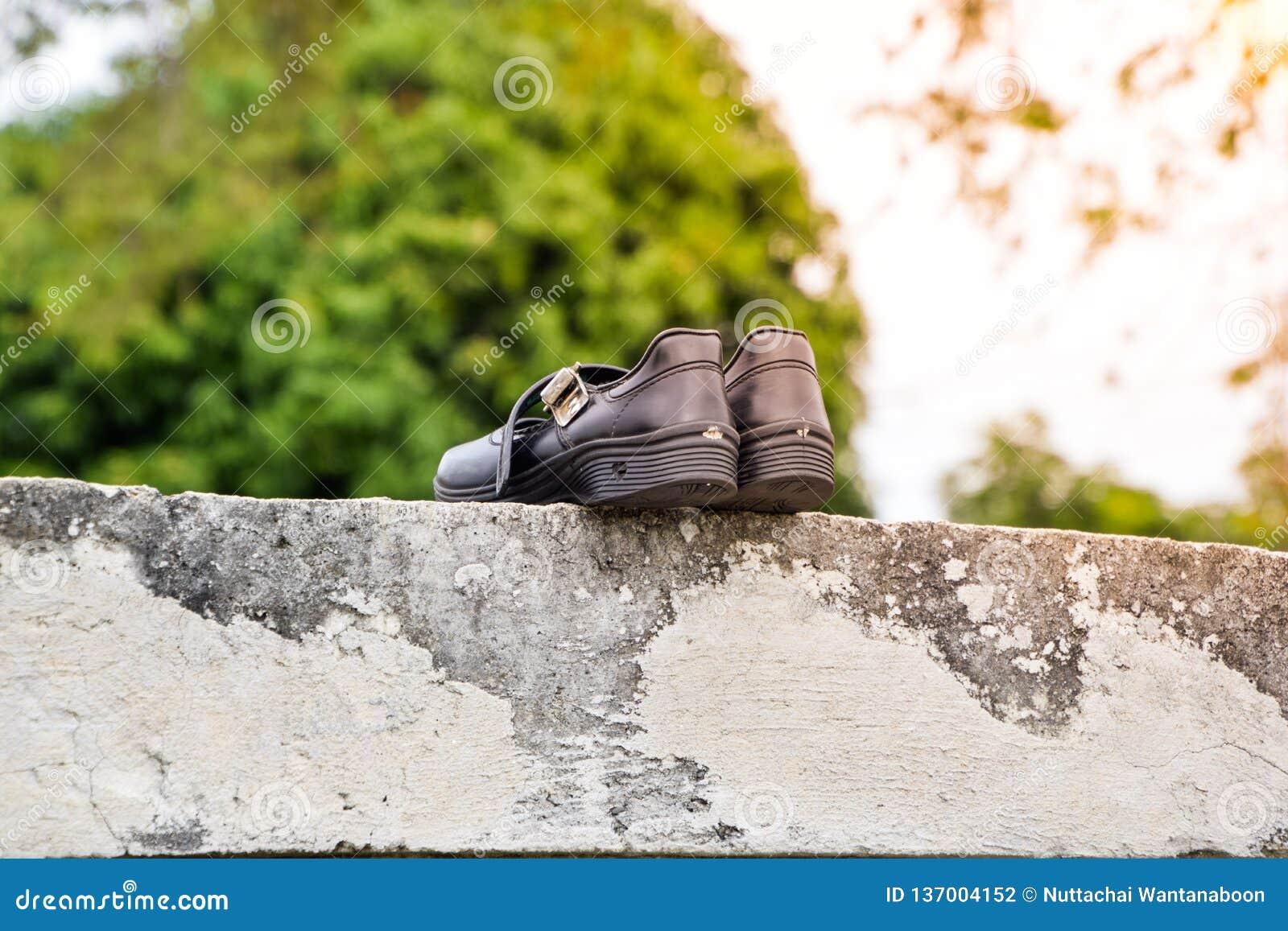 Сухие черные ботинки студента в солнце