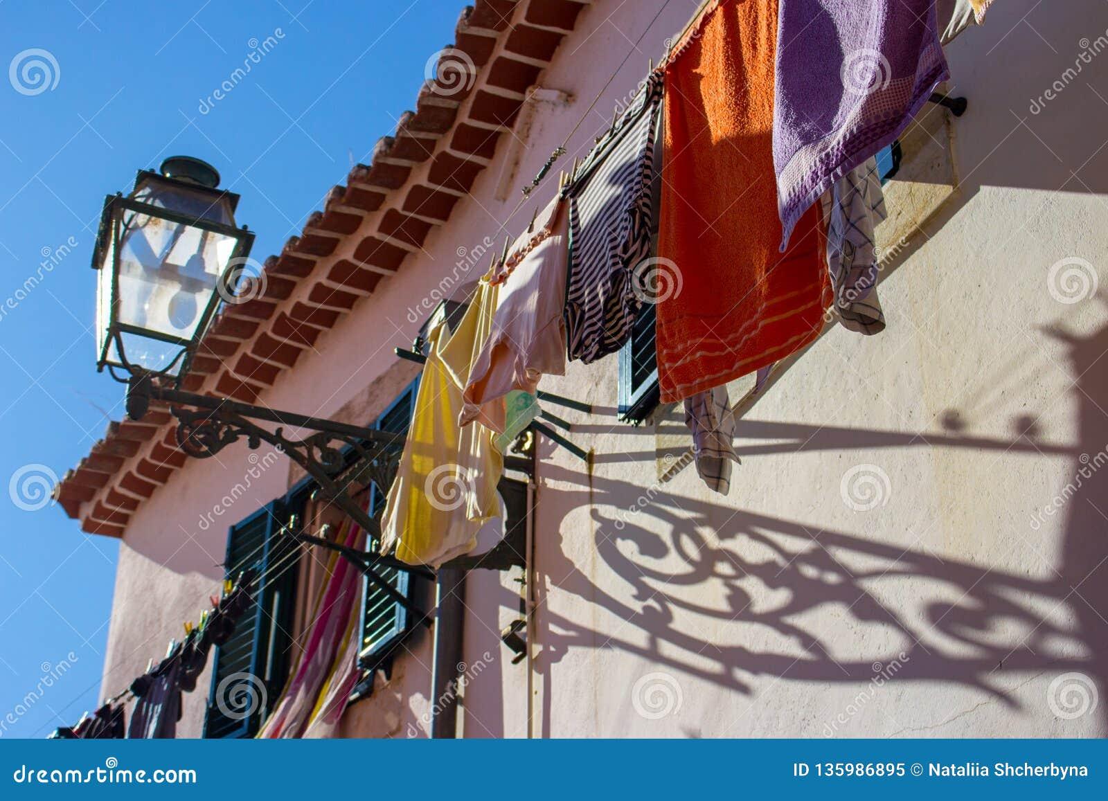 Сушить одежды вне дома с фонариком улицы в Португалии Открытое окно и белье сушить Традиционный домочадец в Португалии
