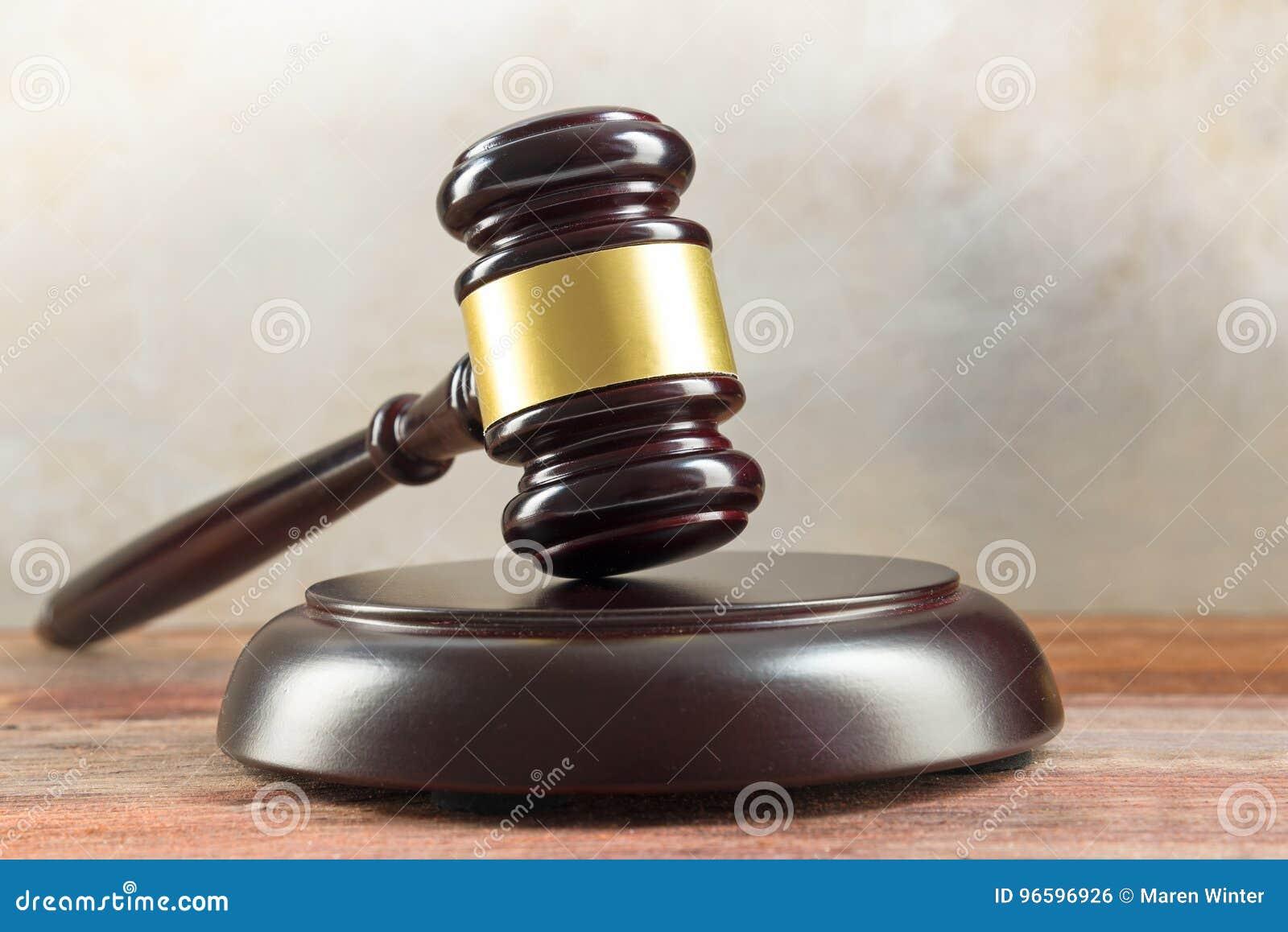 Судите молоток и резонансное устройство на деревянном столе, символ правосудия и