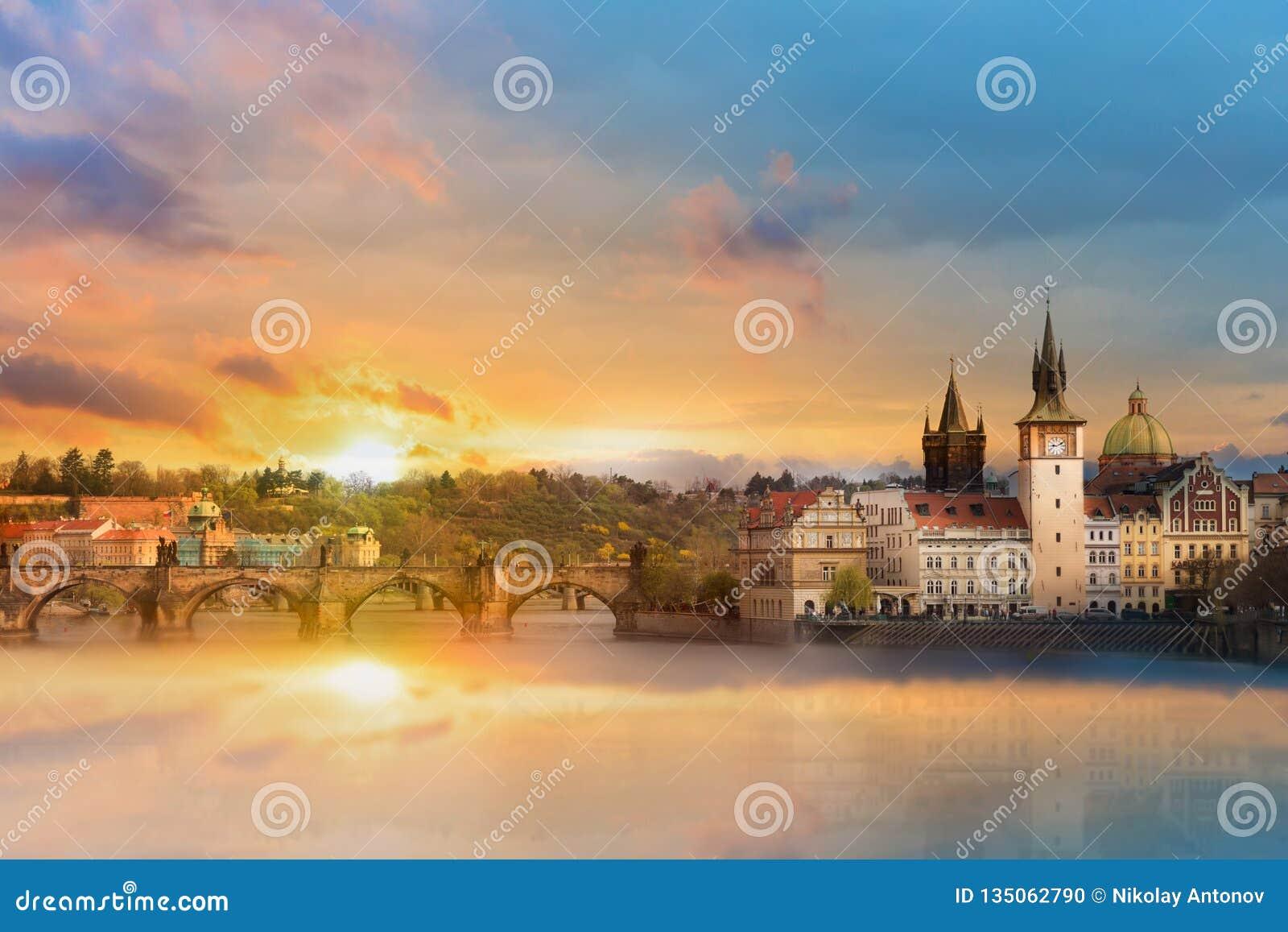 Сценарный взгляд лета старых зданий городка, реки Карлова моста и Влтавы в Праге во время изумляя захода солнца, чехии