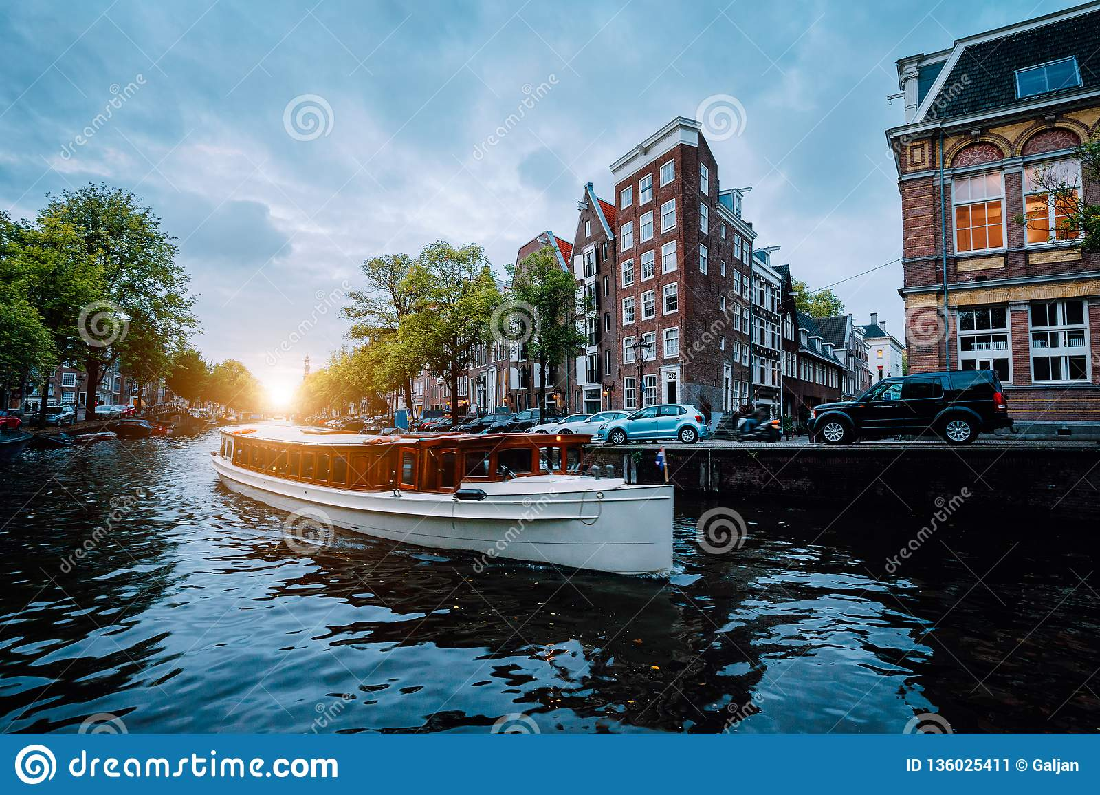 Сцена захода солнца в городе Амстердама Большая туристская шлюпка на известном голландском канале плавая опрокинутые дома Цветаст