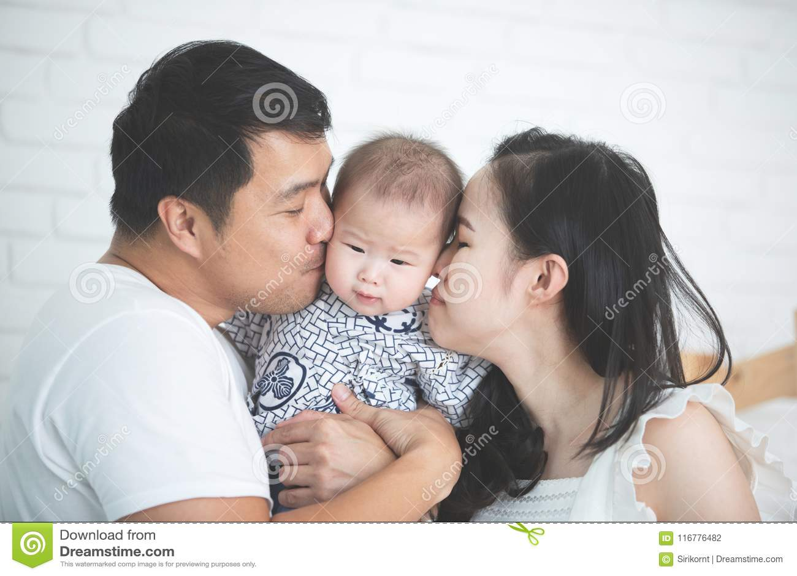 Счастливая азиатская мать отца семьи при дочь целуя с smil