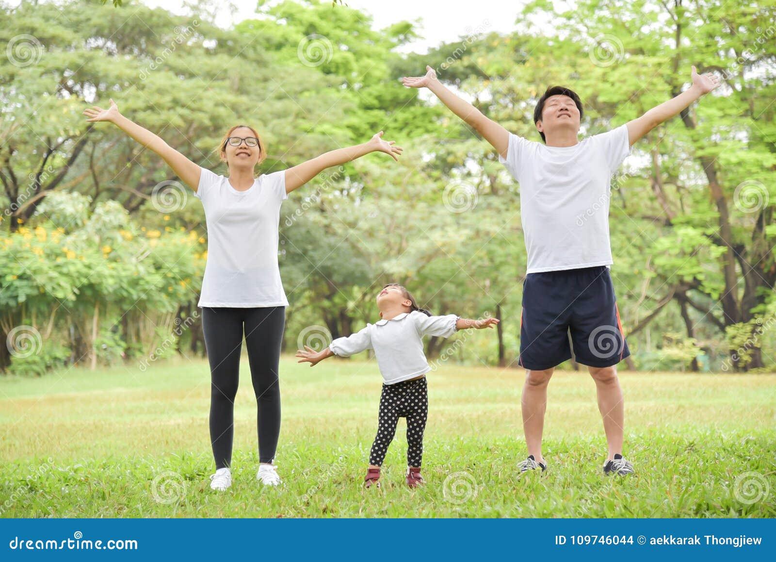 Счастливая азиатская разминка семьи на парке