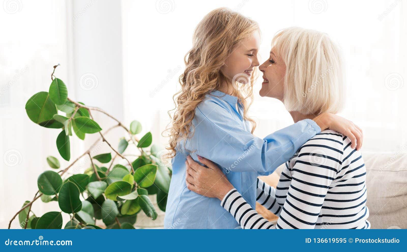Счастливая бабушка и внучка касаясь носам дома