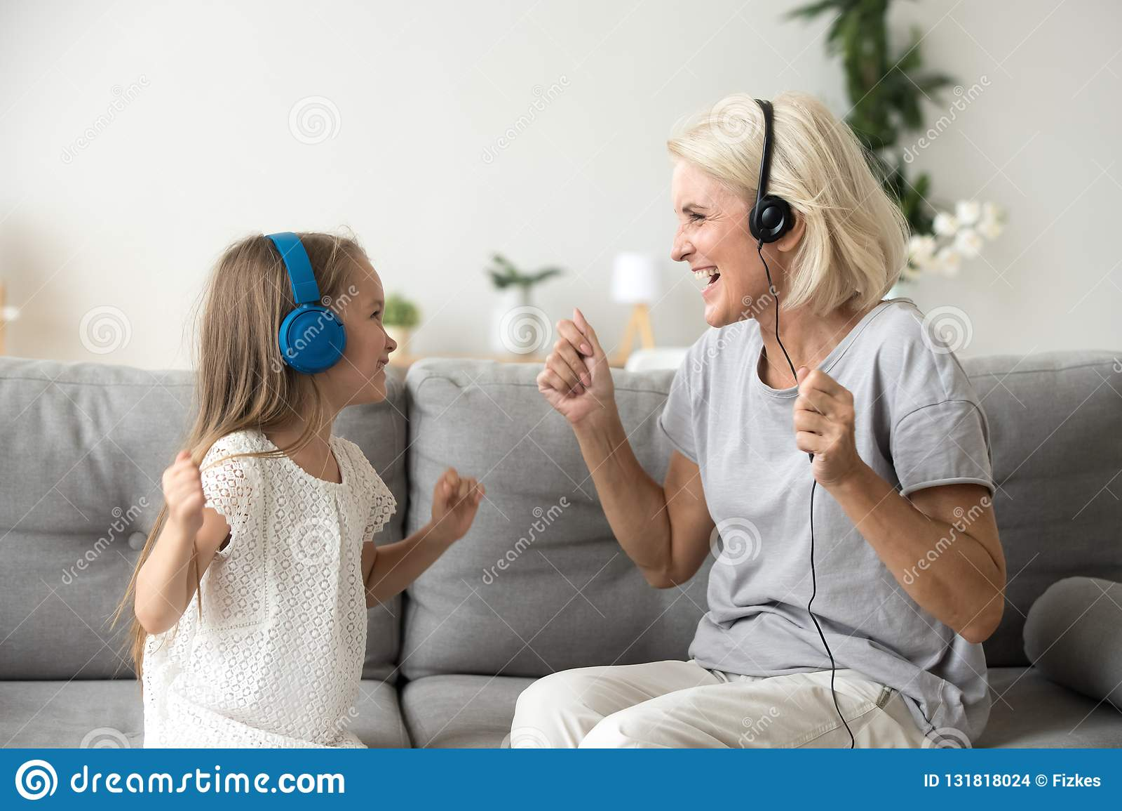 Счастливая бабушка и внучка слушая музыку в headph