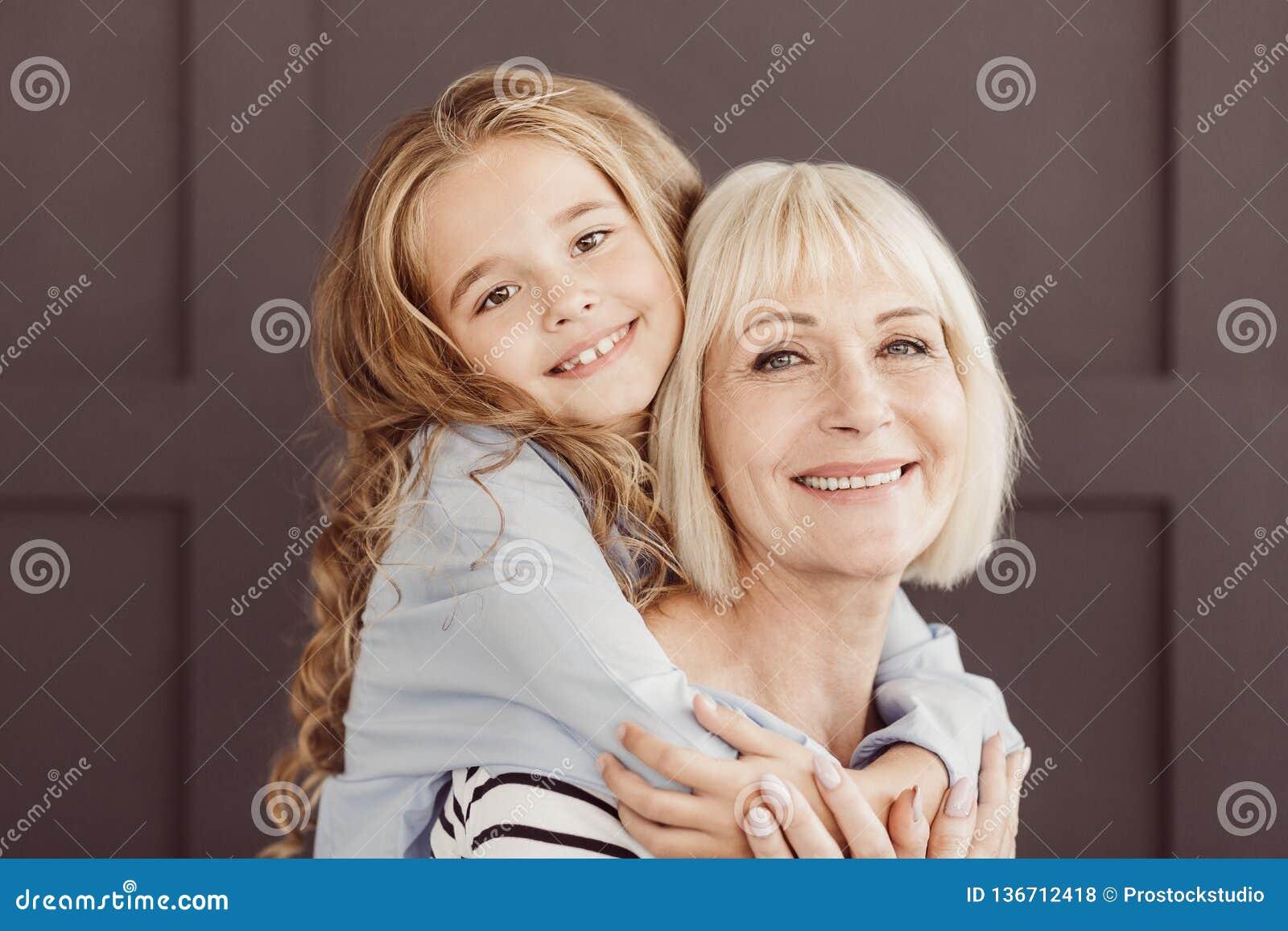 Счастливая бабушка и девушка смотря камеру над коричневой стеной