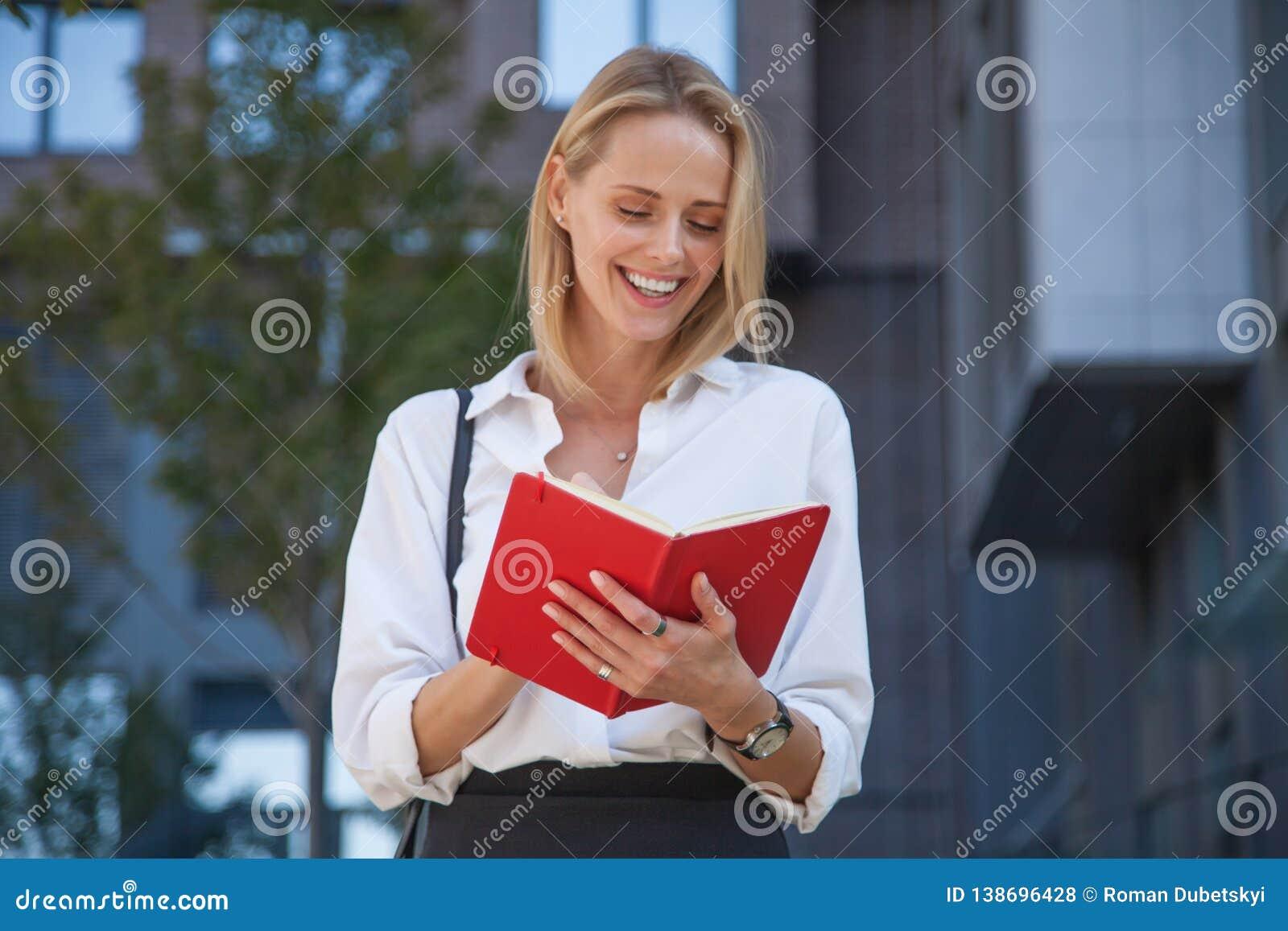 Счастливая белокурая бизнес-леди с тетрадью против офисного здания