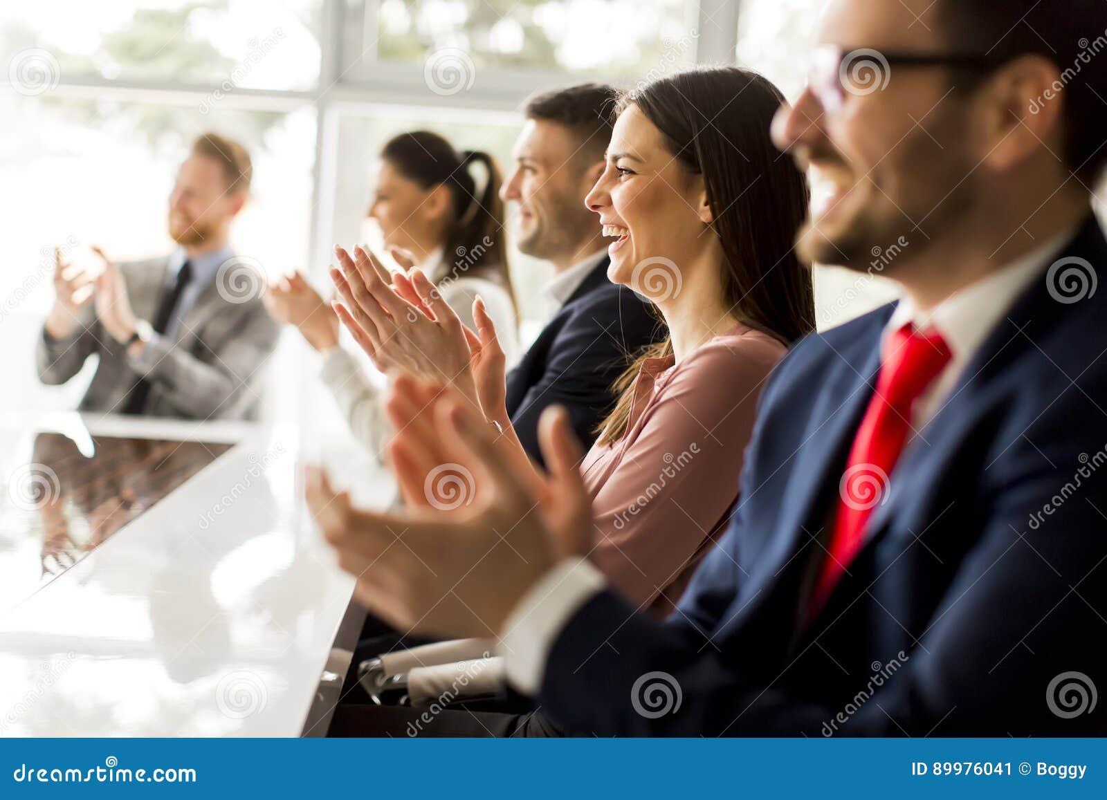 Счастливая группа в составе предприниматели хлопая в офисе