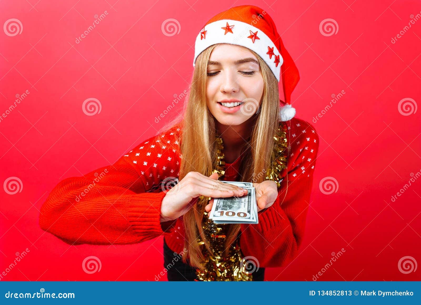 Счастливая девушка в шляпе рождества и с сусалью на ее шеи, с долларами в ее руках, тратит изолированные деньги на красная предпо