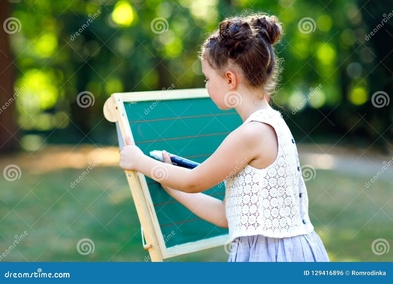 Счастливая девушка маленького ребенка готовя большие Preschool или schoolkid стола мела на первый день элементарного класса задня