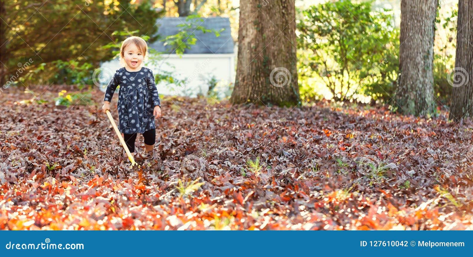 Счастливая девушка малыша сгребая листья