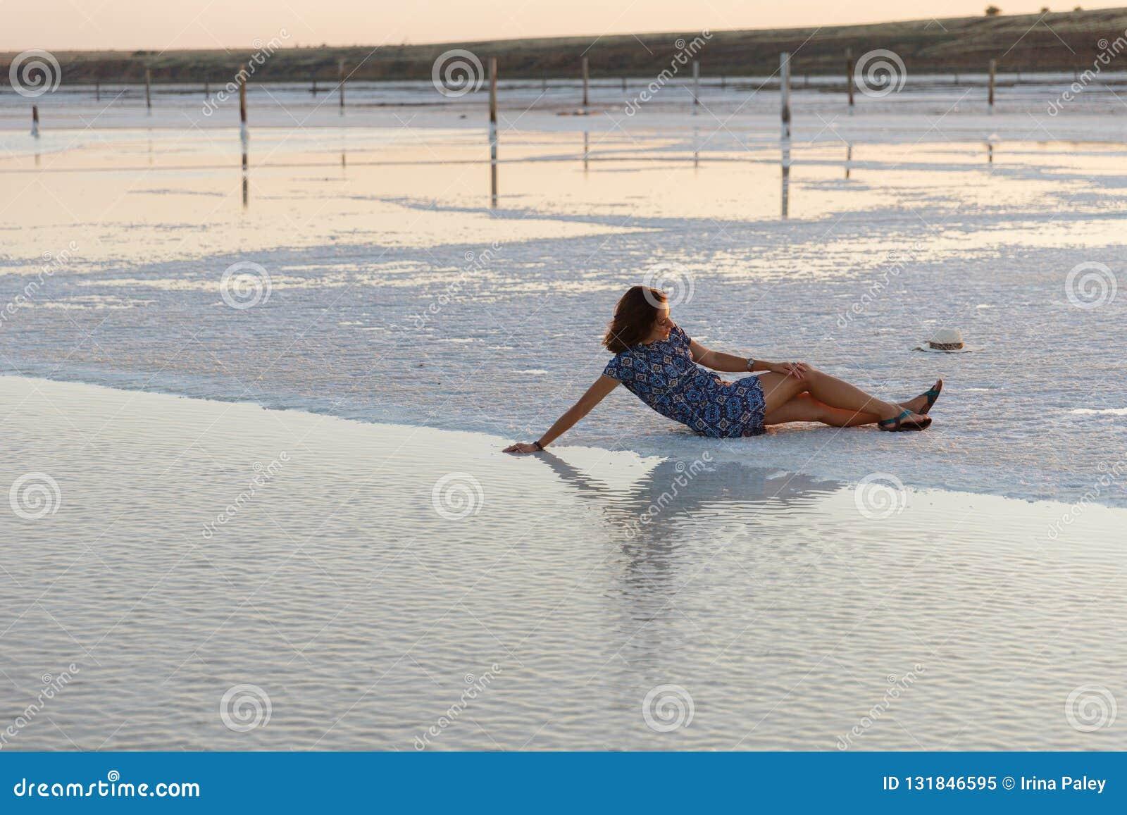 Счастливая девушка наслаждаясь заходом солнца, касается воде озера соли сидя на кристаллах