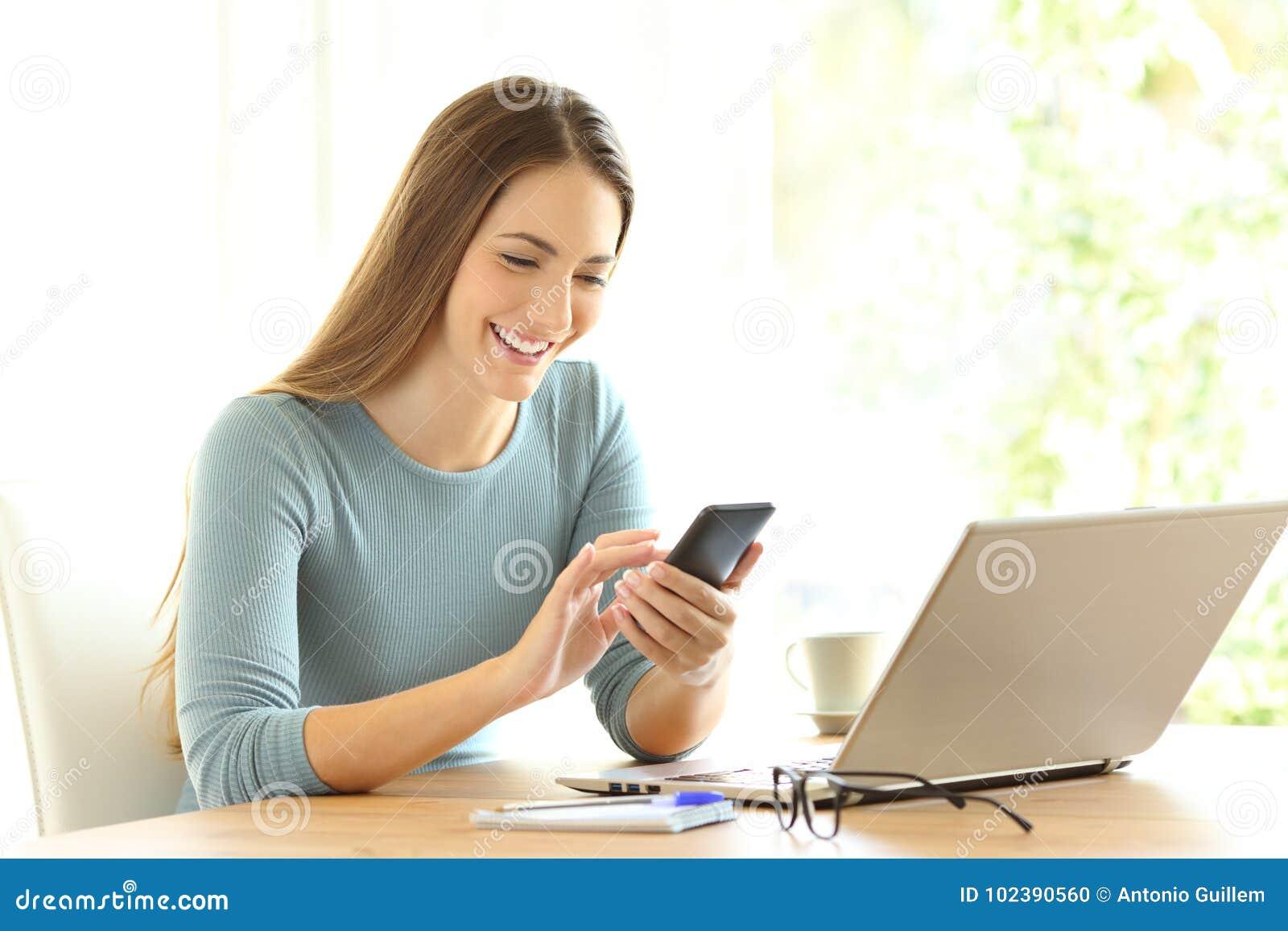 Счастливая девушка проверяя на линии содержании на умном телефоне