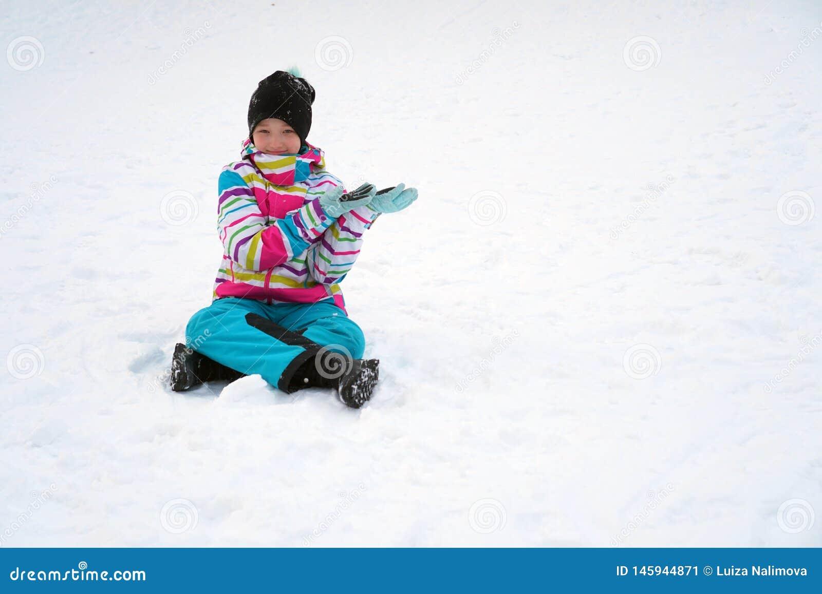 Счастливая девушка сидя на снеге в зиме Ребенок в костюме лыжи с ее руками показывает на космосе экземпляра