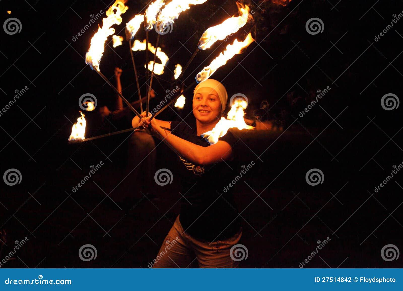 Счастливая девушка juggler играя с пожаром