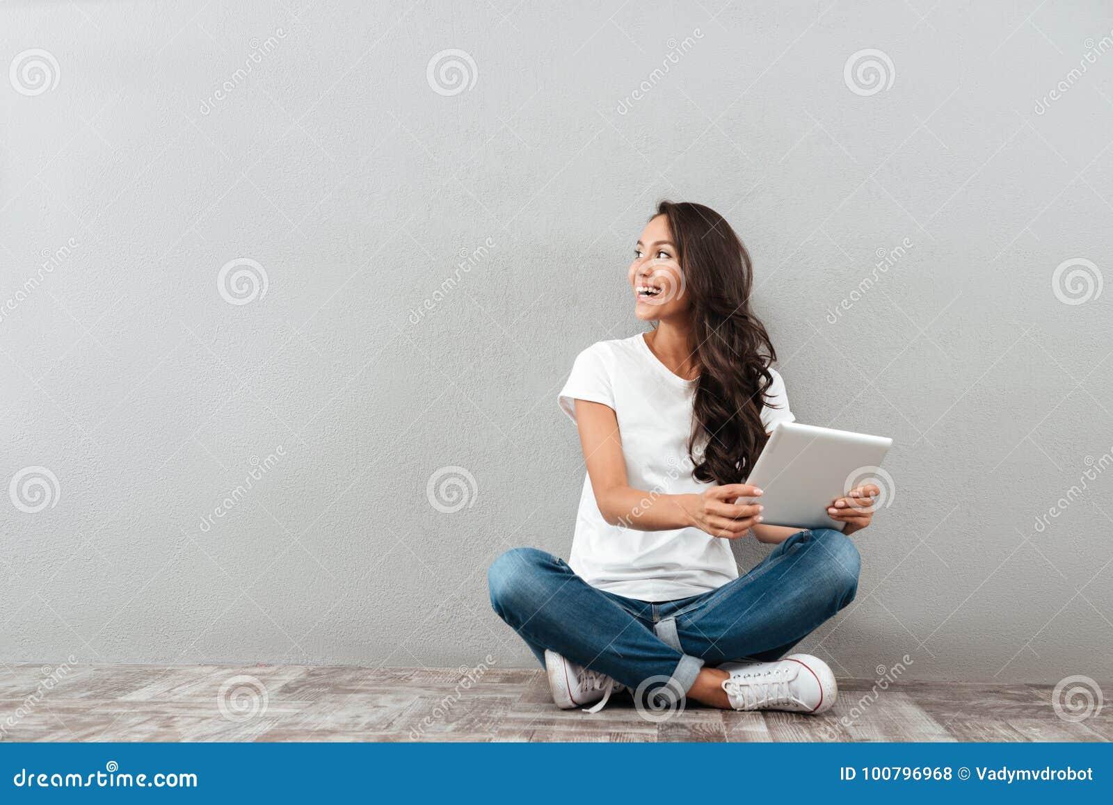 Счастливая довольно азиатская женщина держа планшет