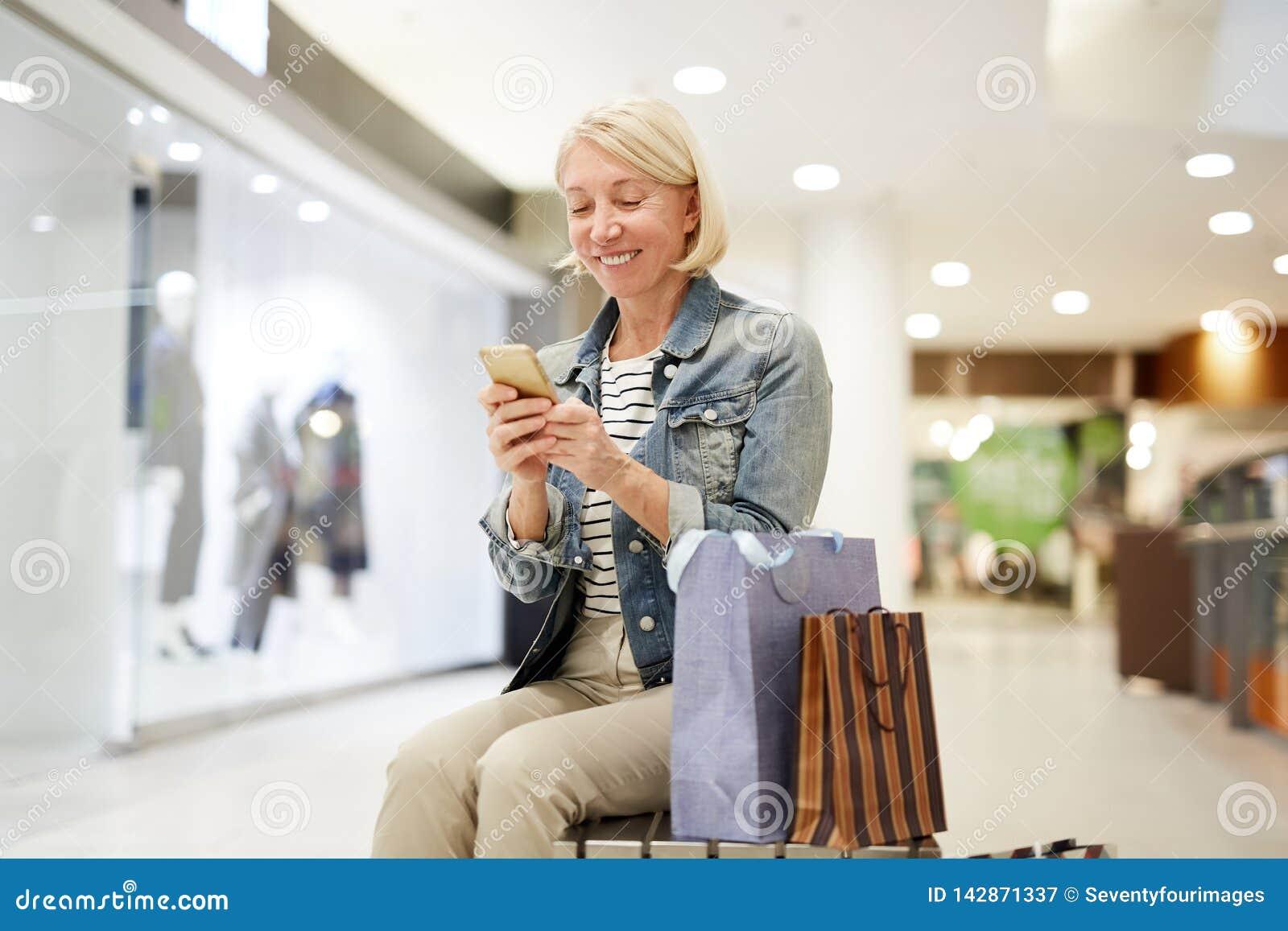 Счастливая женщина делая столб о покупках на социальных средствах массовой информации