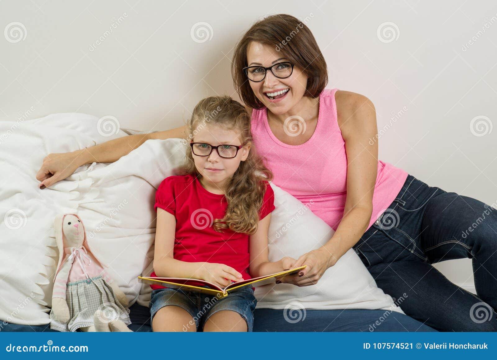 Счастливая женщина при ее ребенок дочери, читая совместно книгу дома