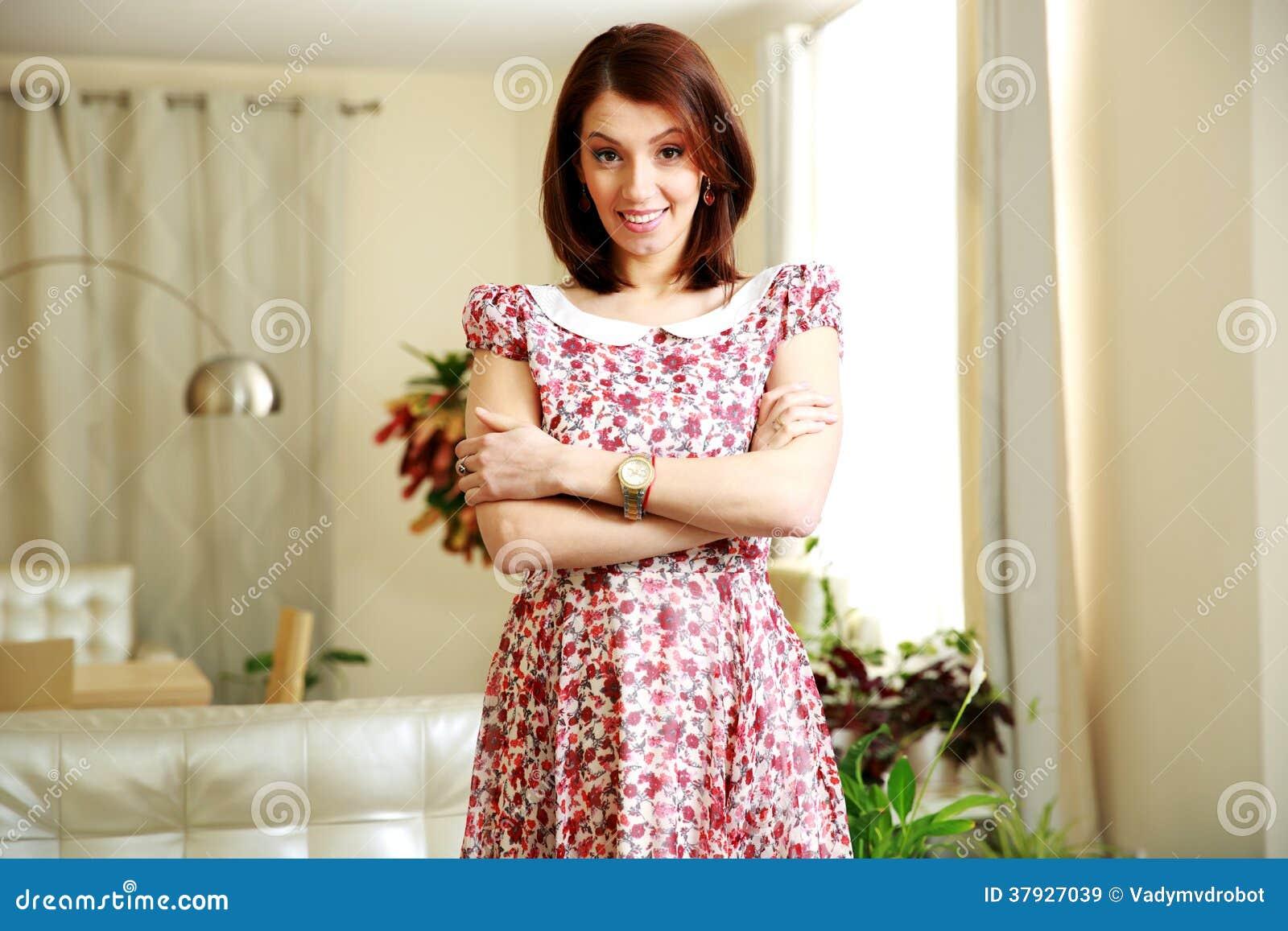 Счастливая женщина стоя при сложенные оружия