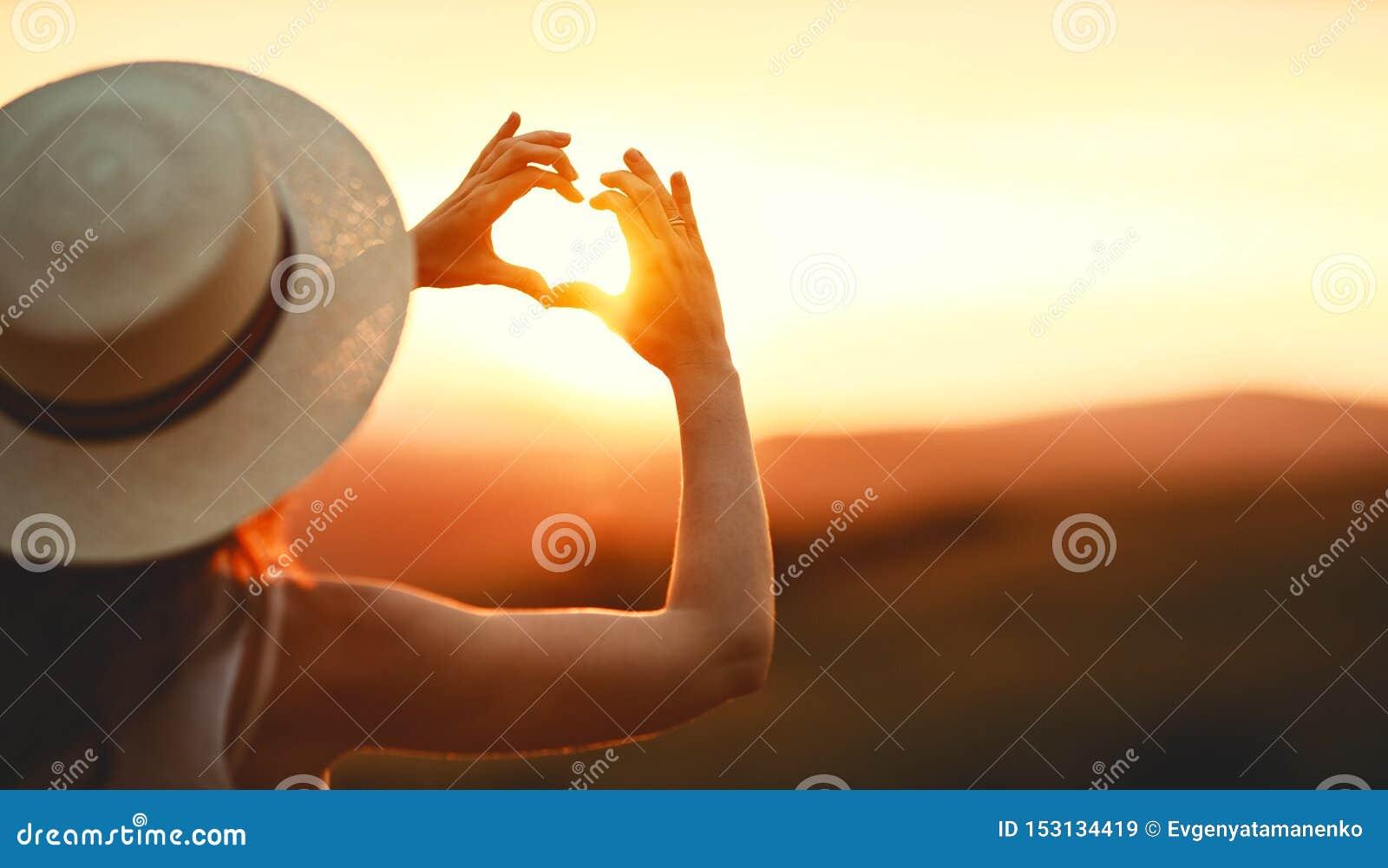 Счастливая женщина с ладонями ваших пальцев в форме сердца на заходе солнца в природе