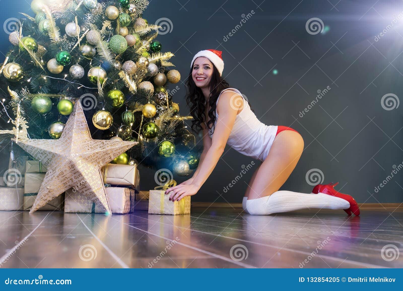 Счастливая женщина с подарком под рождественской елкой Молодая сексуальная красивая девушка в женском белье и крышке Санта Клауса