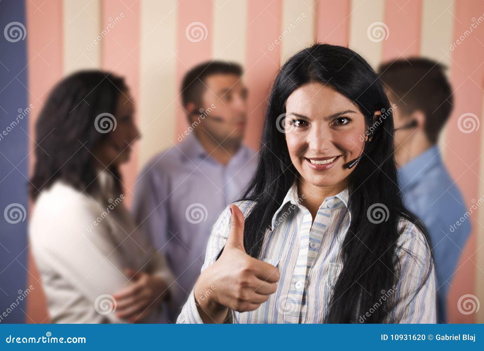 Счастливая женщина центра телефонного обслуживания давая большие пальцы руки вверх
