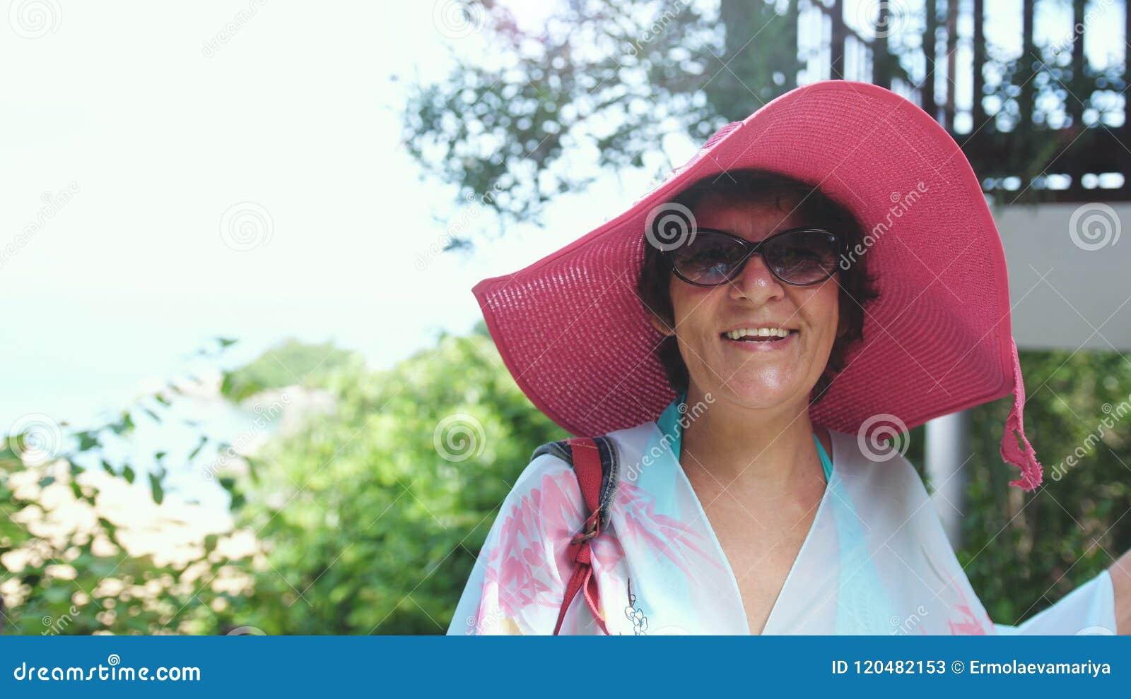 Счастливая зрелая женщина в розовых шляпе и солнечных очках в тропическом курорте на отпуске