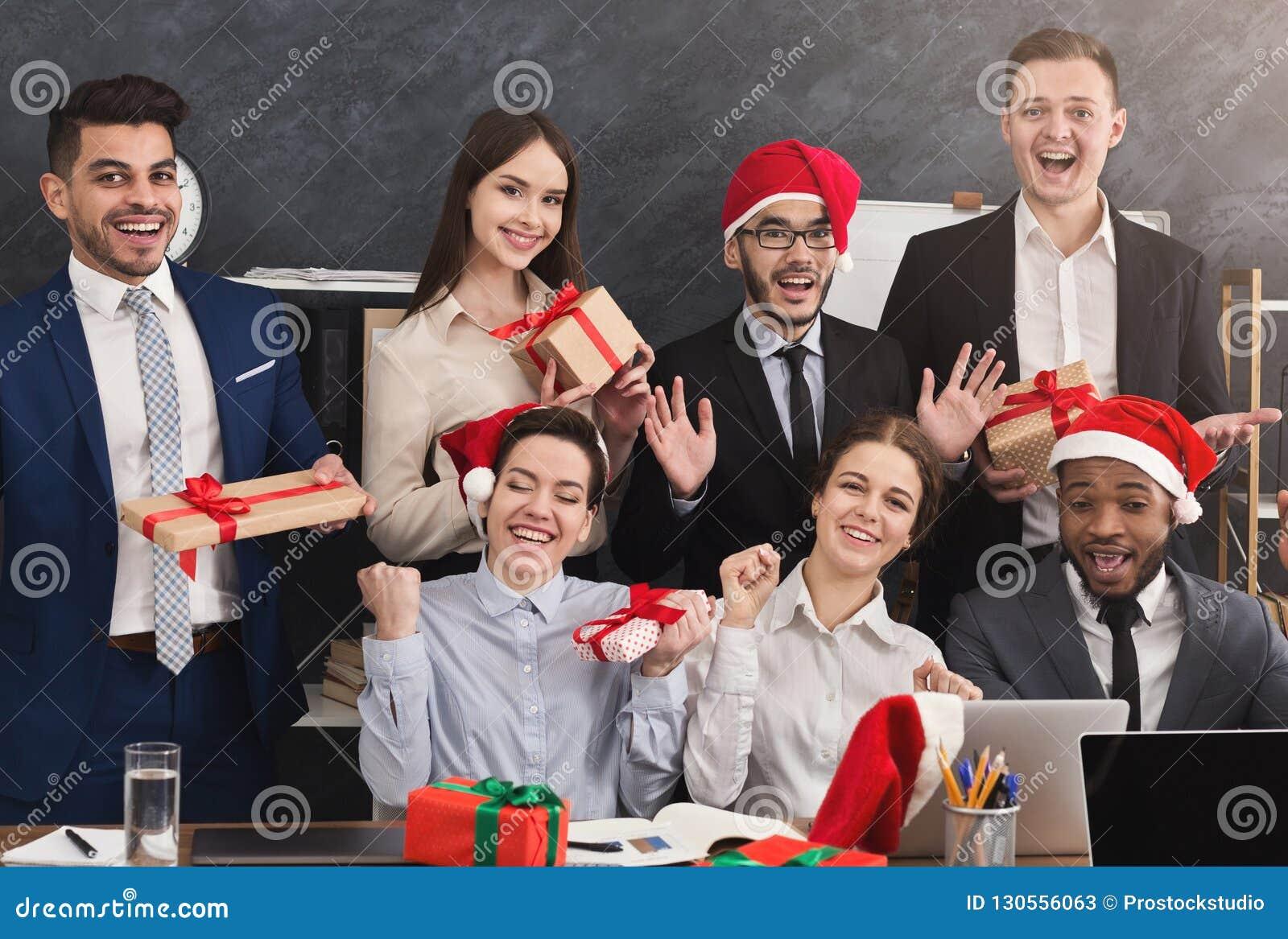 Счастливая команда дела наслаждаясь рождественской вечеринкой в офисе