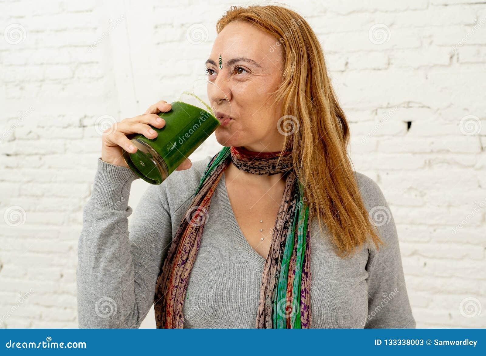 Счастливая красивая женщина усмехаясь и выпивая здоровый smoothie свежего овоща в здоровом образе жизни