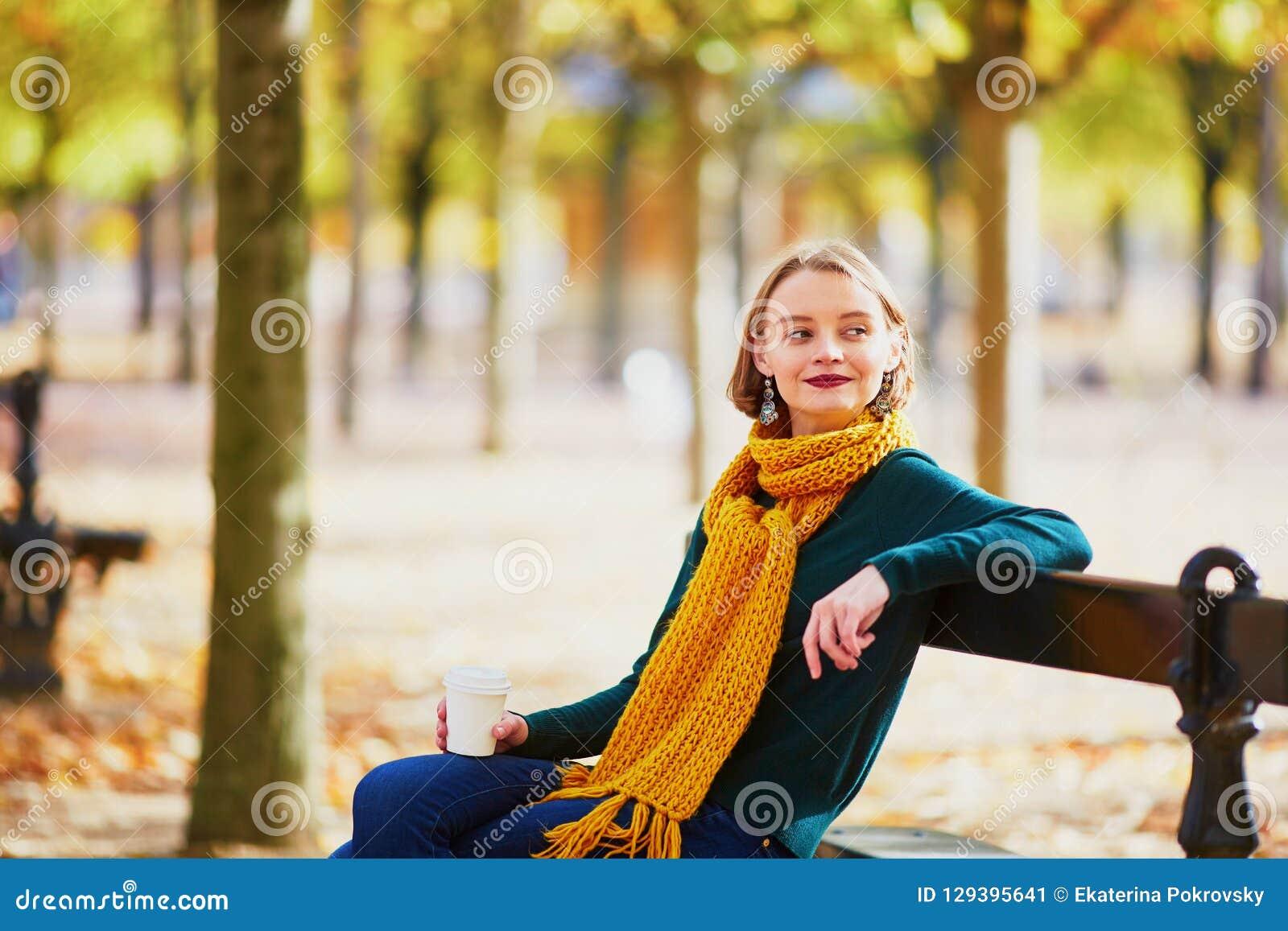 Счастливая маленькая девочка в желтом шарфе идя в парк осени