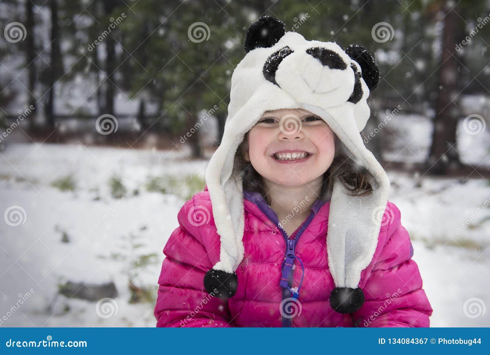 Счастливая маленькая девочка в розовой куртке снега