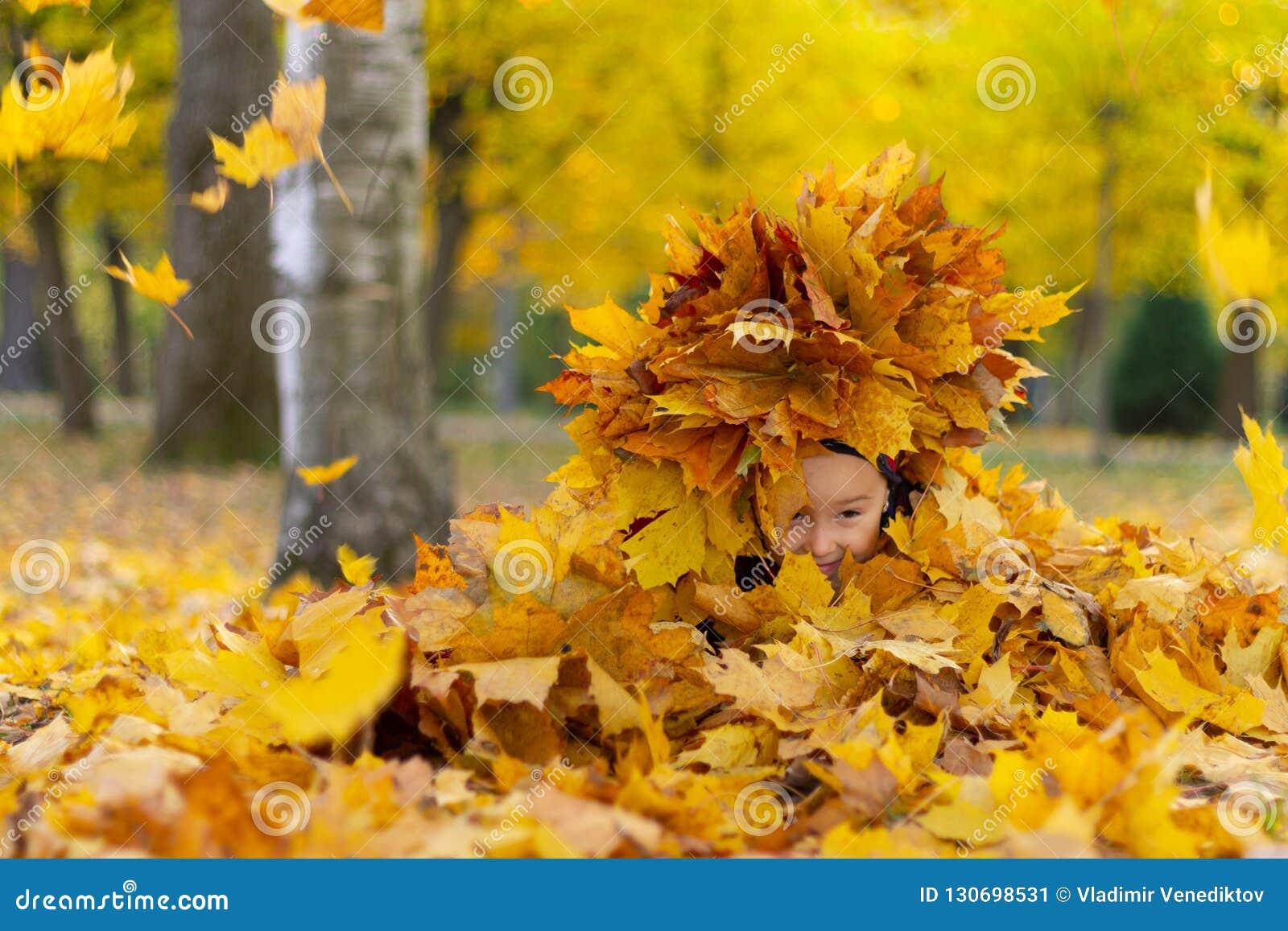 Счастливая маленькая девочка играет с листьями осени в парке