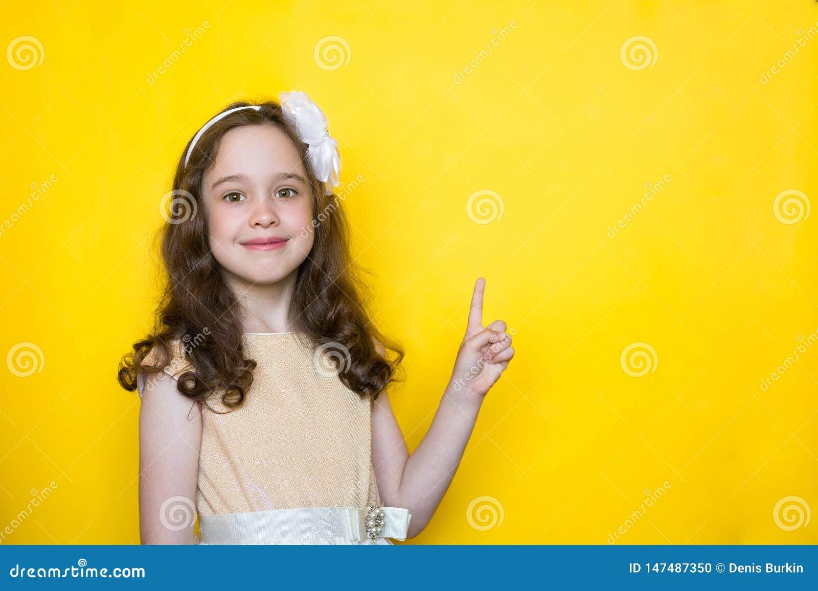 Счастливая маленькая девочка на желтых пунктах предпосылки ее палец на космосе для помечать буквами r