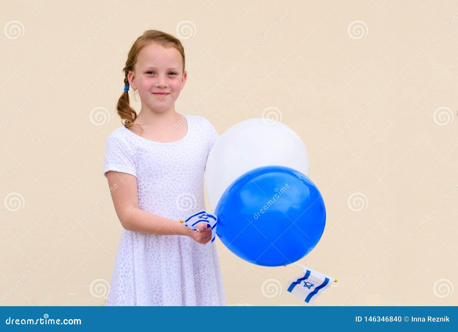 Счастливая маленькая девочка с голубым и белым флагом ans Израиля воздушных шаров