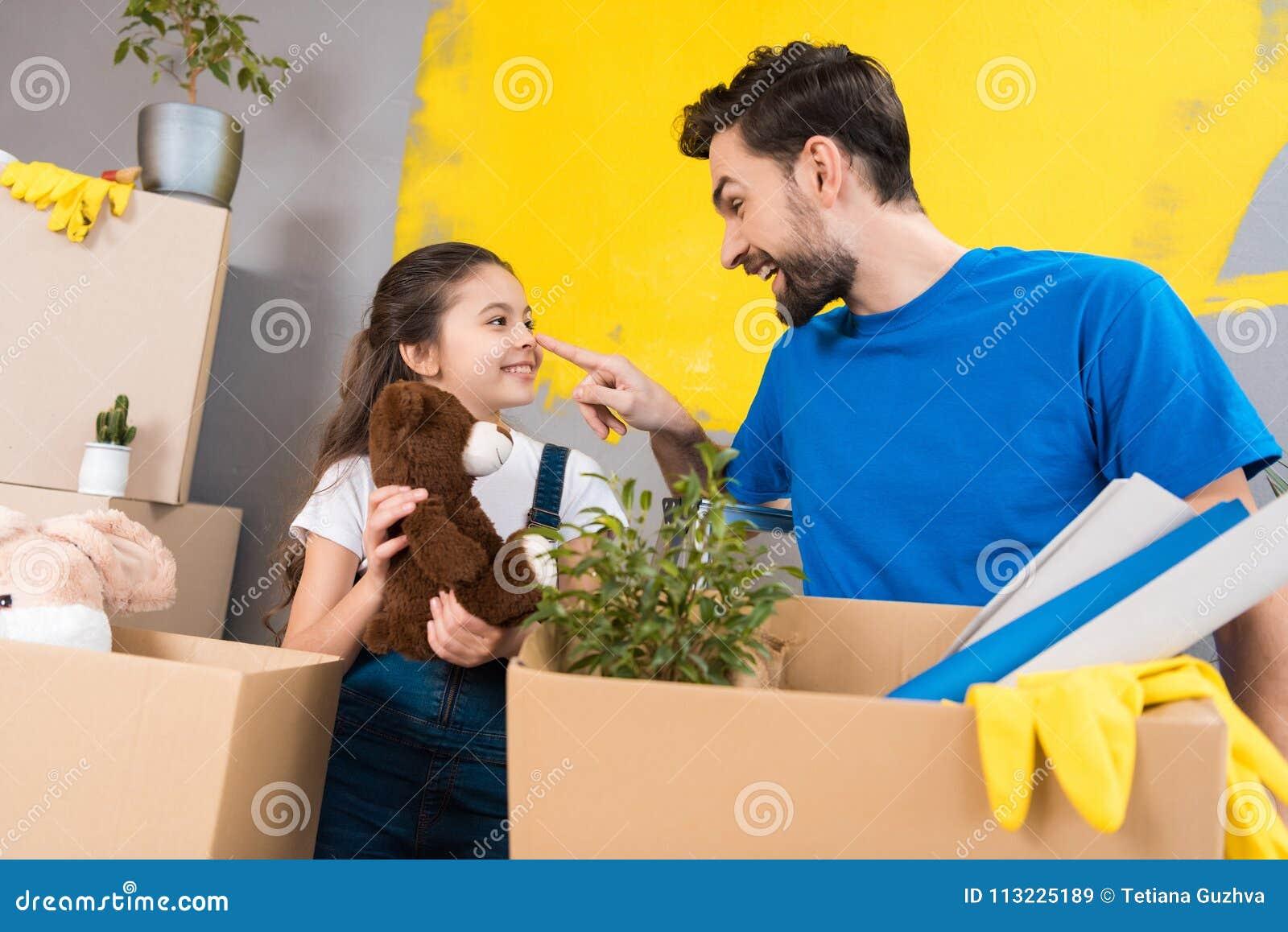 Счастливая маленькая девочка с коробкой игрушек плюша смотрит отца который начал ремонт в доме