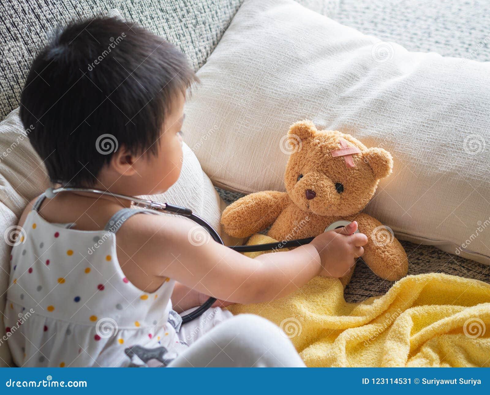 Счастливая маленькая милая девушка играет доктора с стетоскопом и