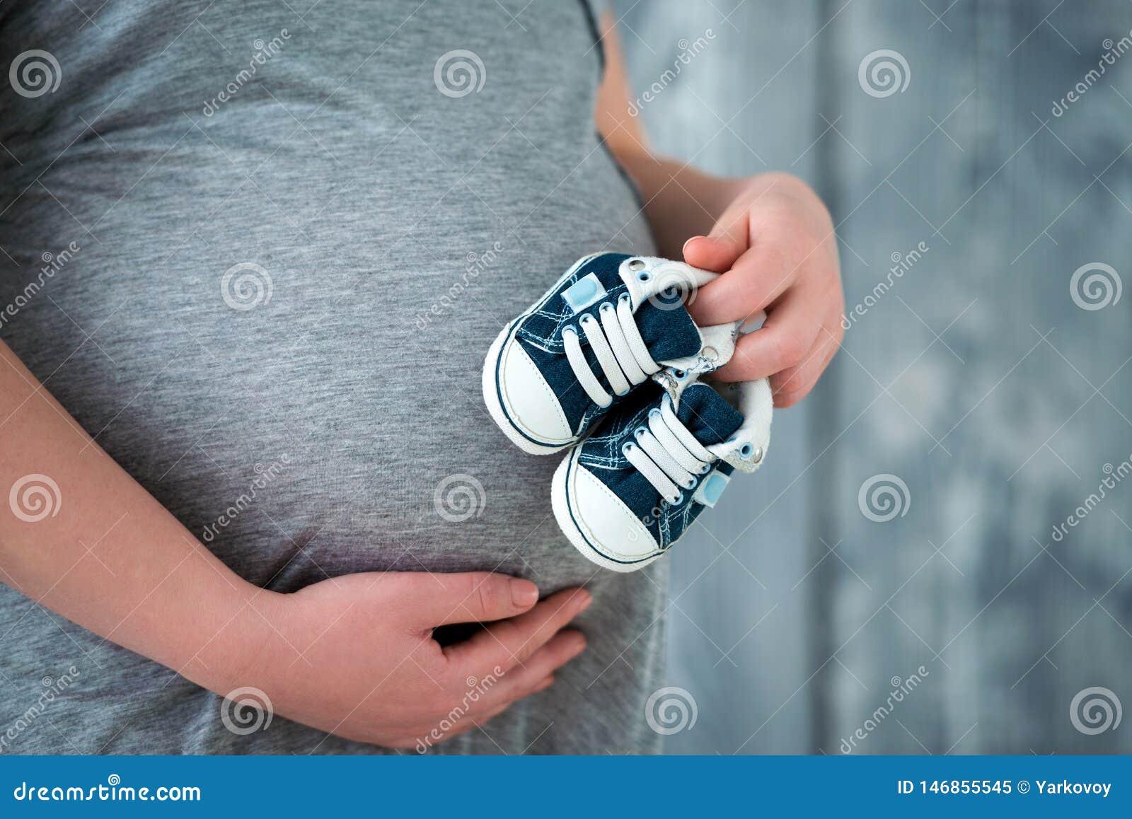 Счастливая мать в ожидании рождение ее сына Тапки добыч младенца удерживания беременной женщины на предпосылке tummy :