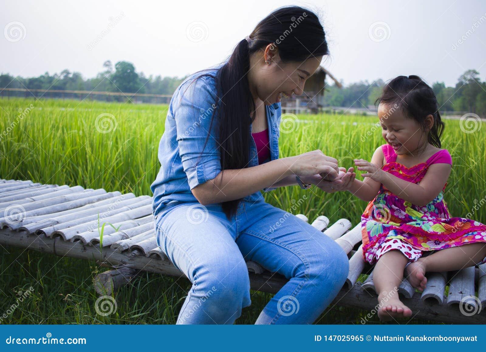 Счастливая мать и ее детская игра outdoors имея потеху, землю зеленого поля риса заднюю