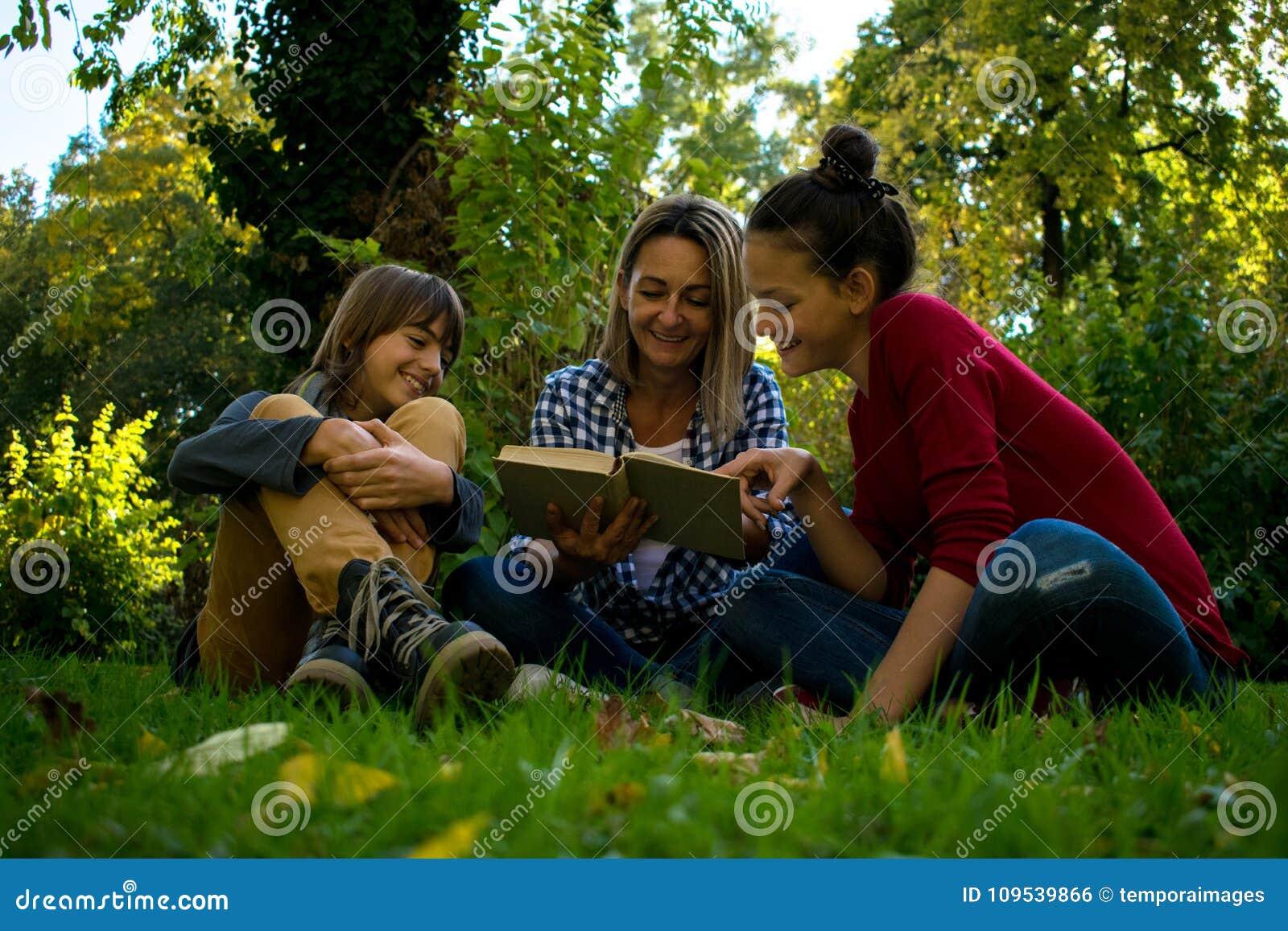 Счастливая мать читая книгу к ее подростковым детям в природе