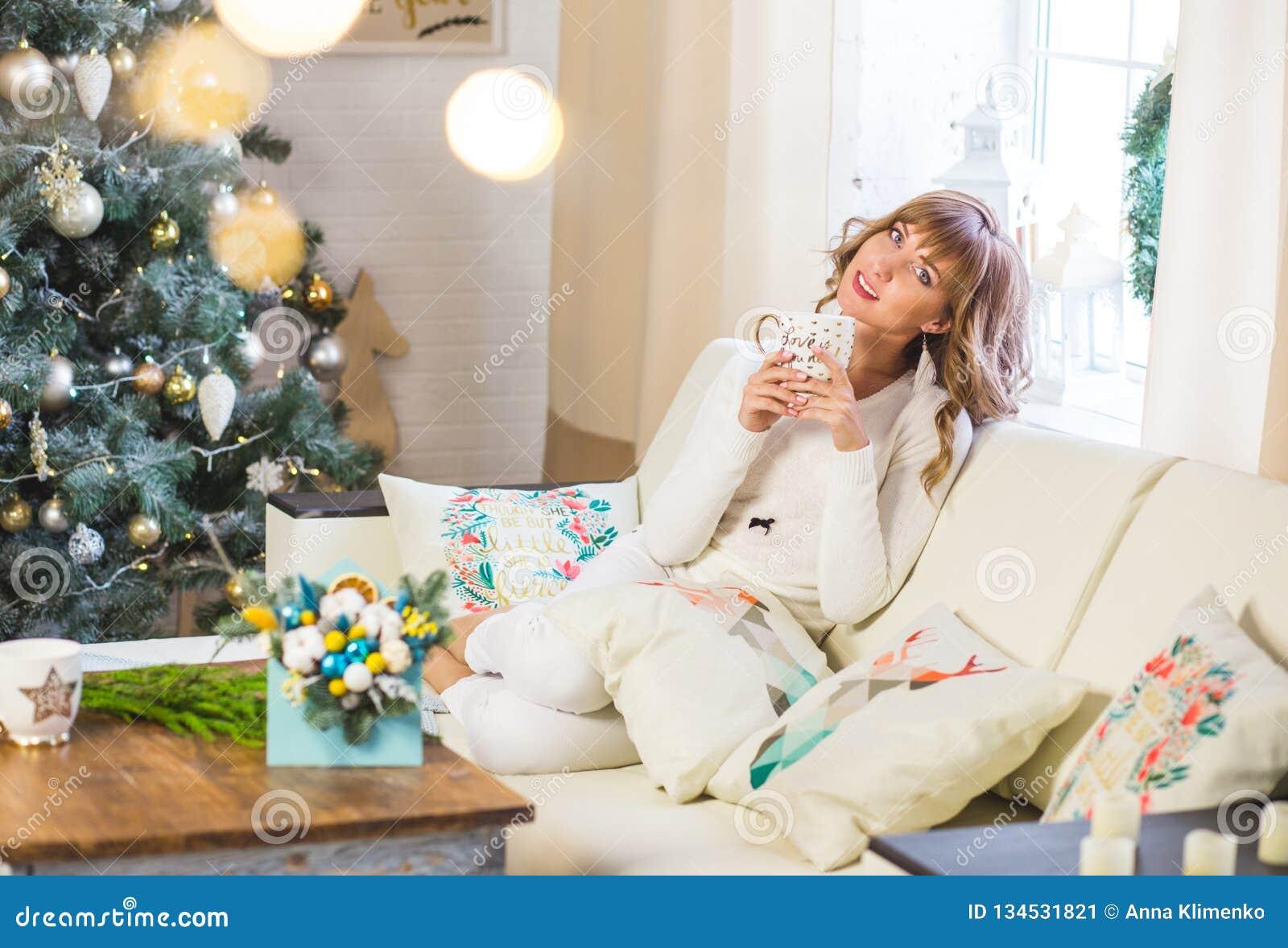 Счастливая молодая дама с вьющиеся волосы сидит около рождественской елки