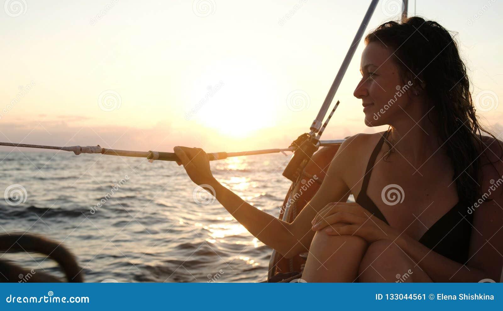 Счастливая молодая женщина в купальнике сидит на в корме плавая яхты на заходе солнца